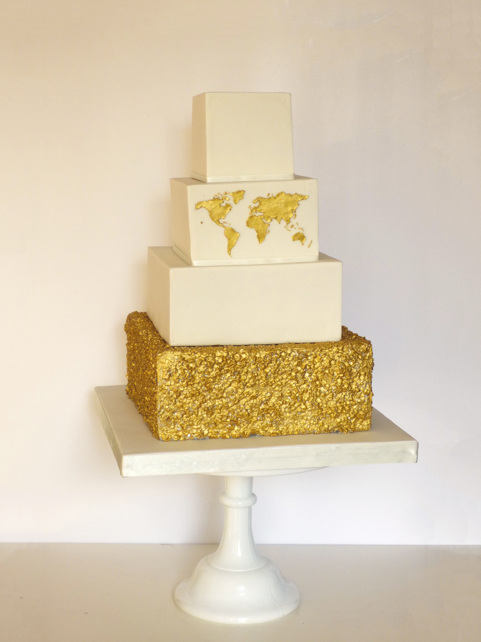 Square cake with gold sequins and gold world map for a travel themed wedding in Central London.