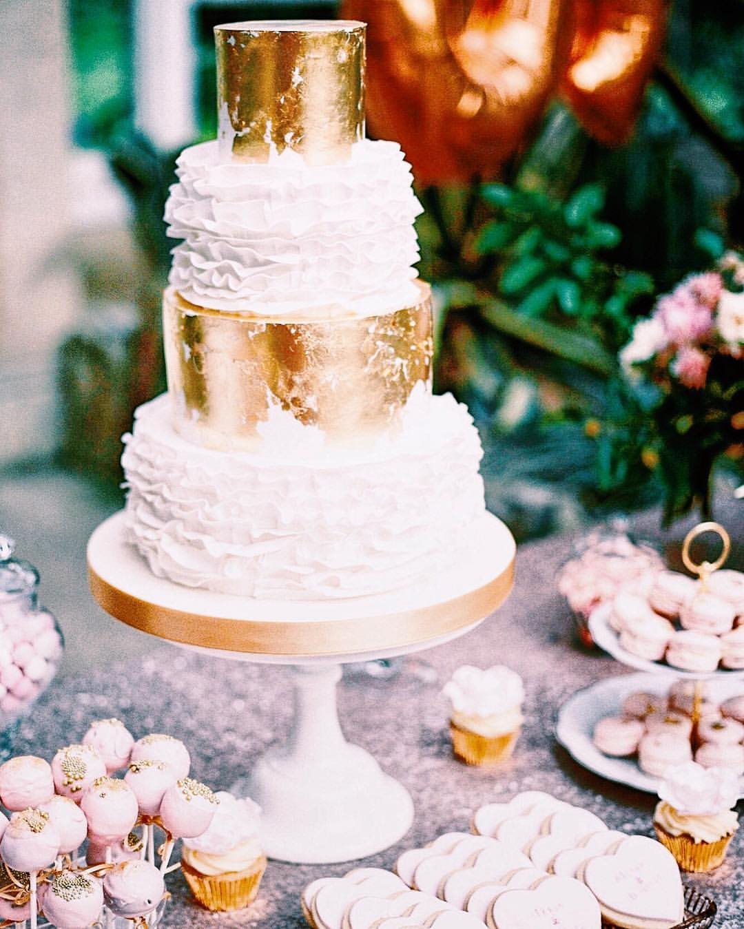 Distressed gold leaf and frilly ruffles give this wedding cake texture, set up as part of a dessert table in West London's Syon Park.
