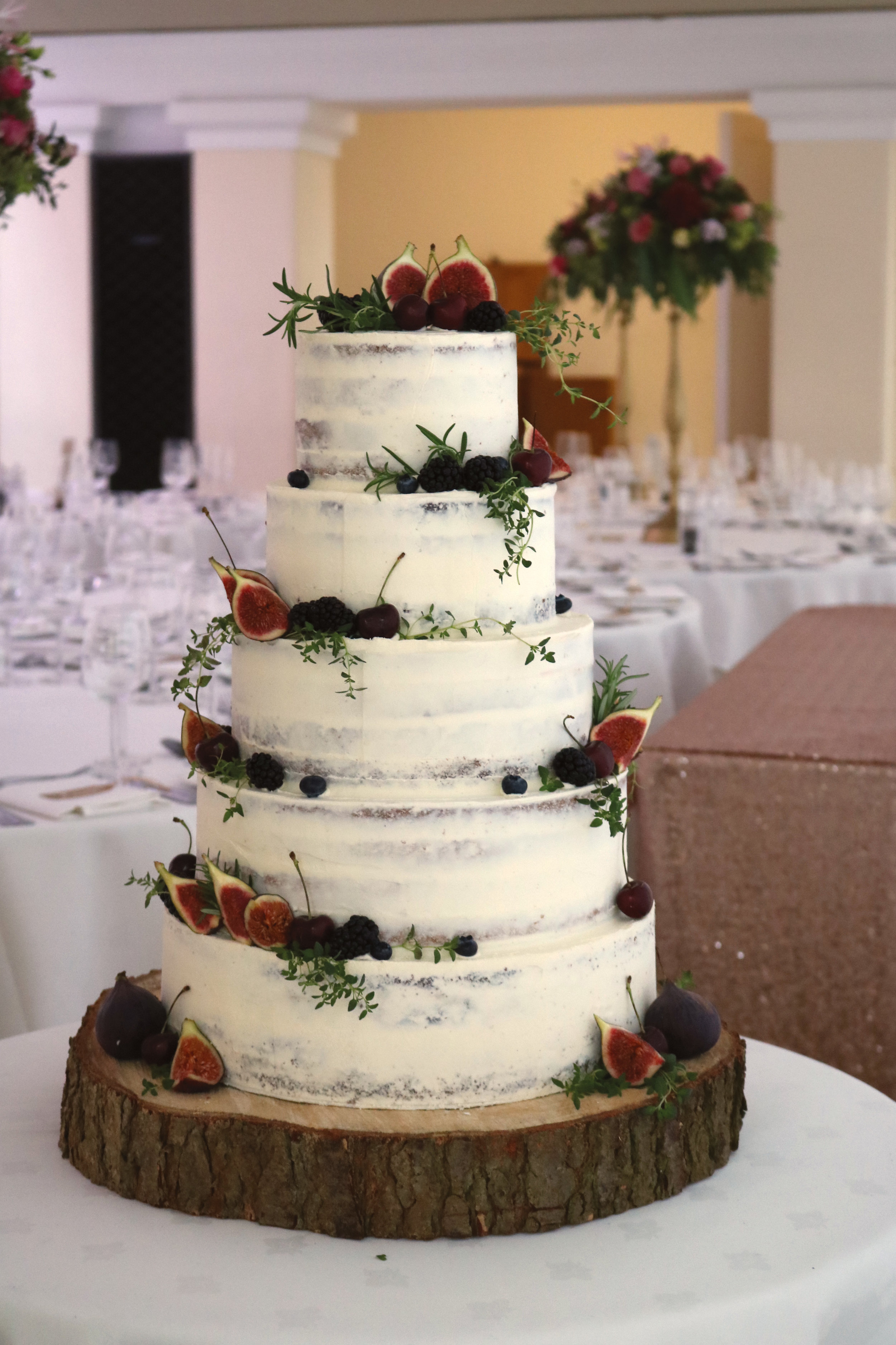 Semi-naked wedding cake finished with fresh fruit (figs, blackberries, cherries etc) at Pembroke Lodge in Richmond Park in West London.