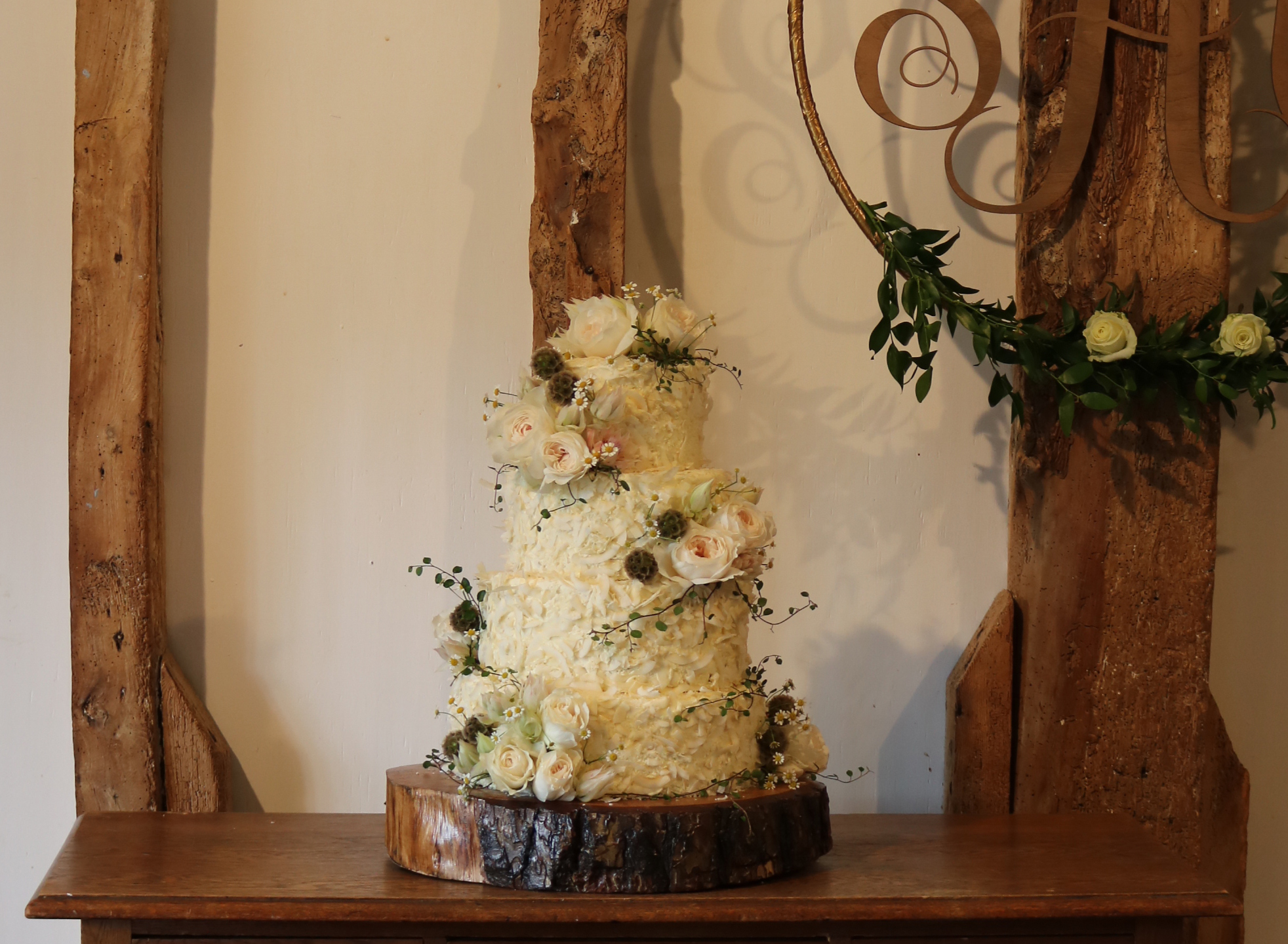 Coconut covered textured wedding cake with beautiful fresh flowers
