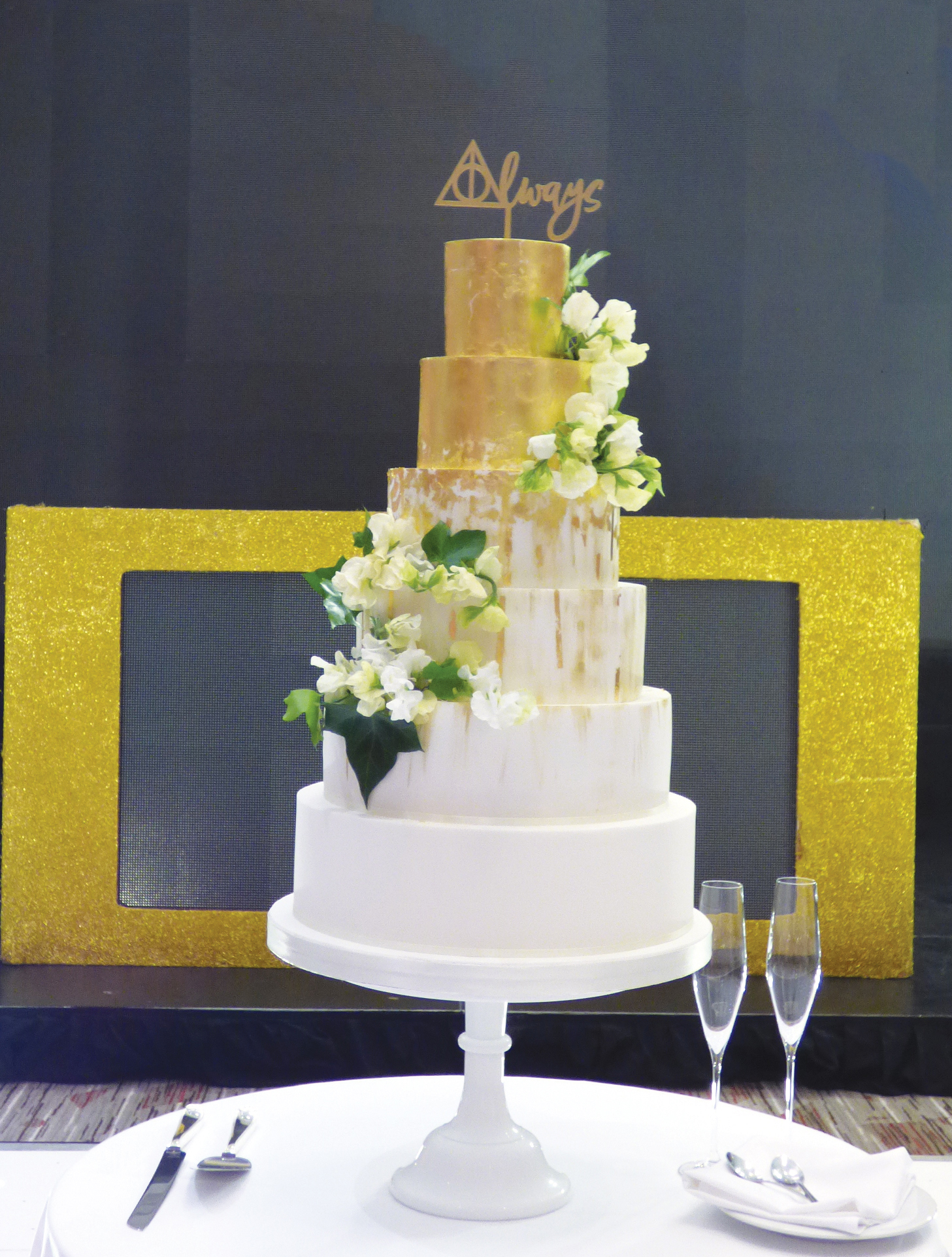 "Gold leaf for a luxe feel that is on trend but doesn't blow the budget, This wedding had a Harry Potter theme to the wedding cake was finished with an ""Always"" cake topper."