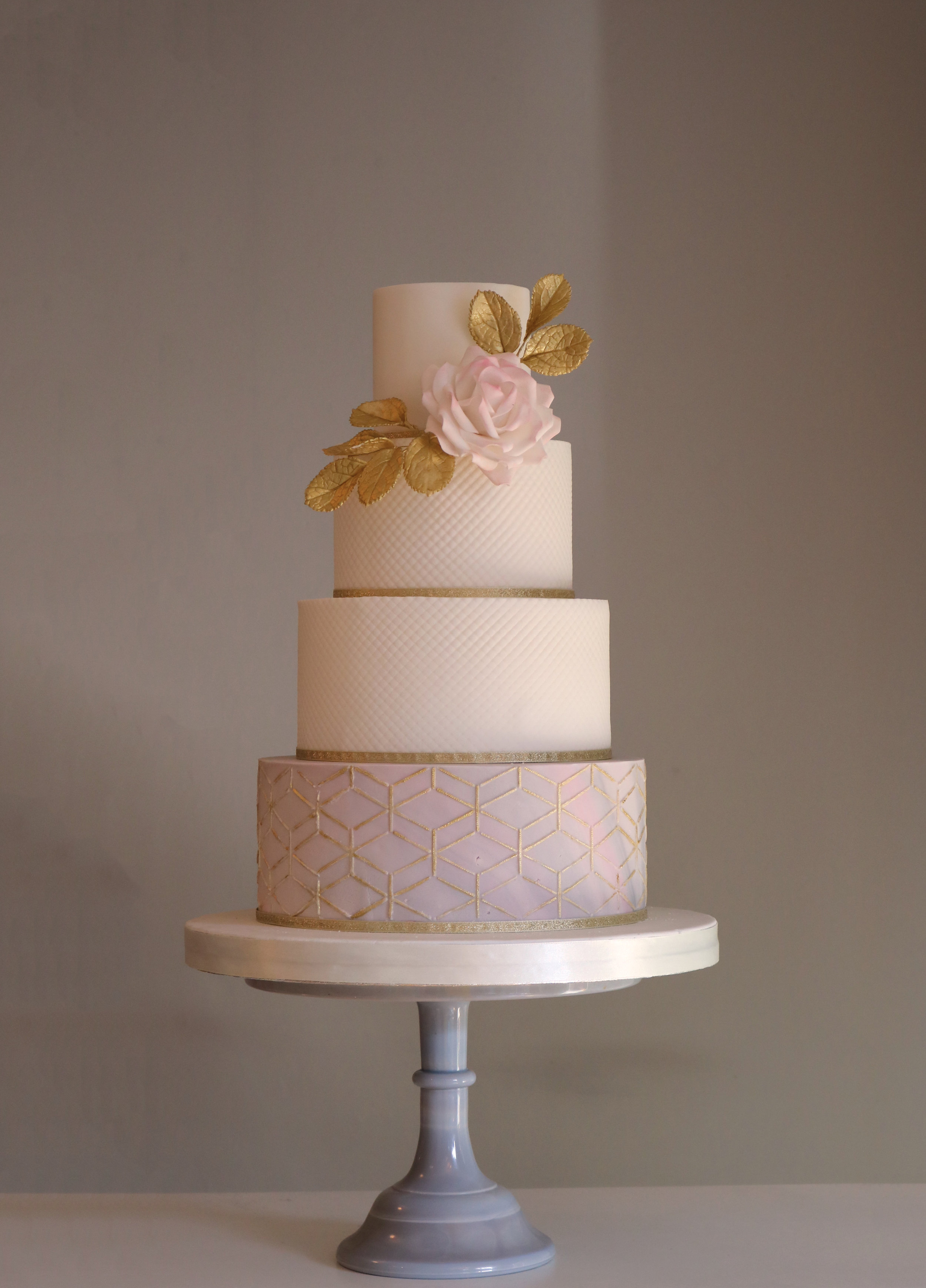 Wedding cake with marbled and textured tiers, with a geometric design.