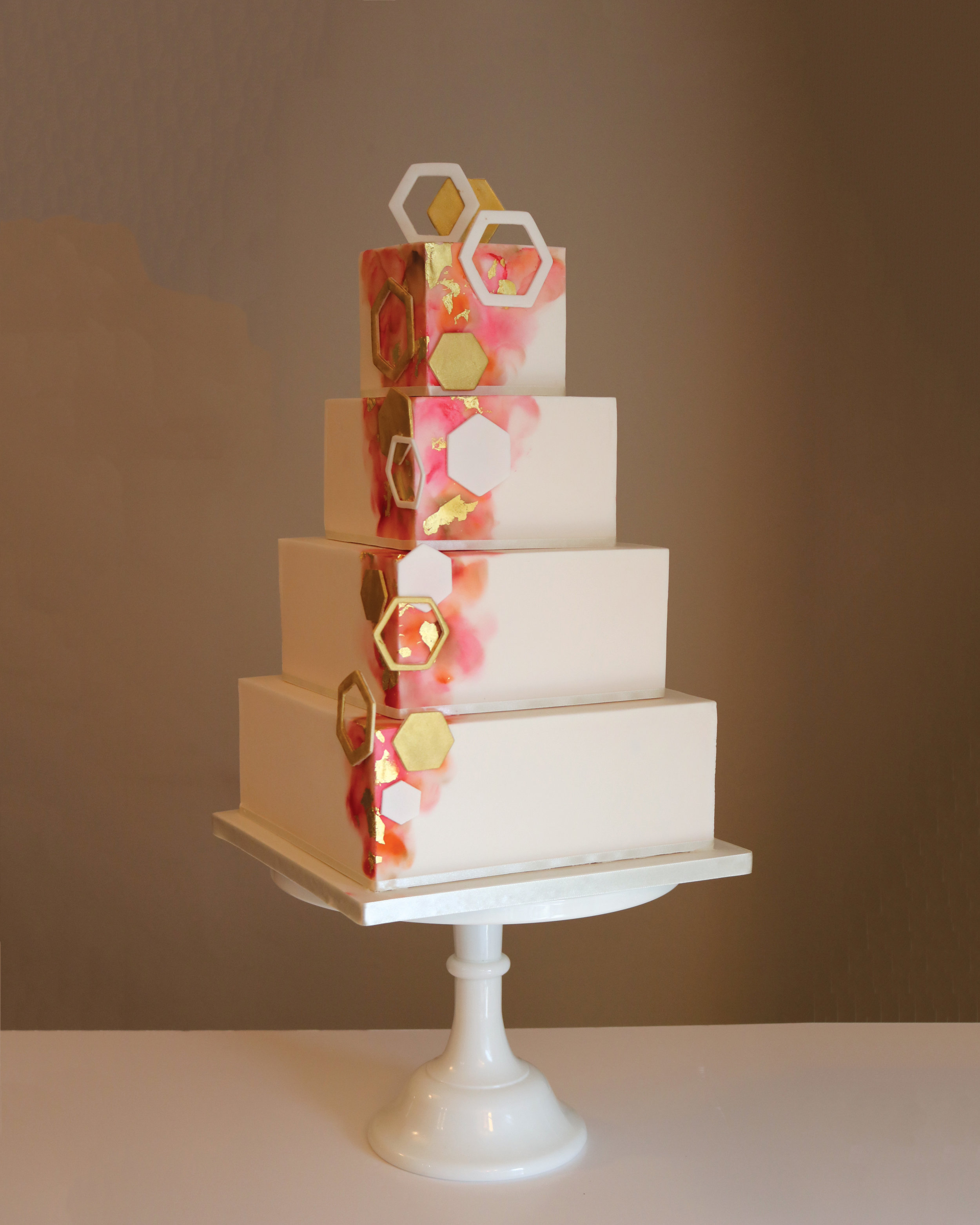 A contemporary modern wedding cake with watercolour painted tiers and metallic gold geometric details