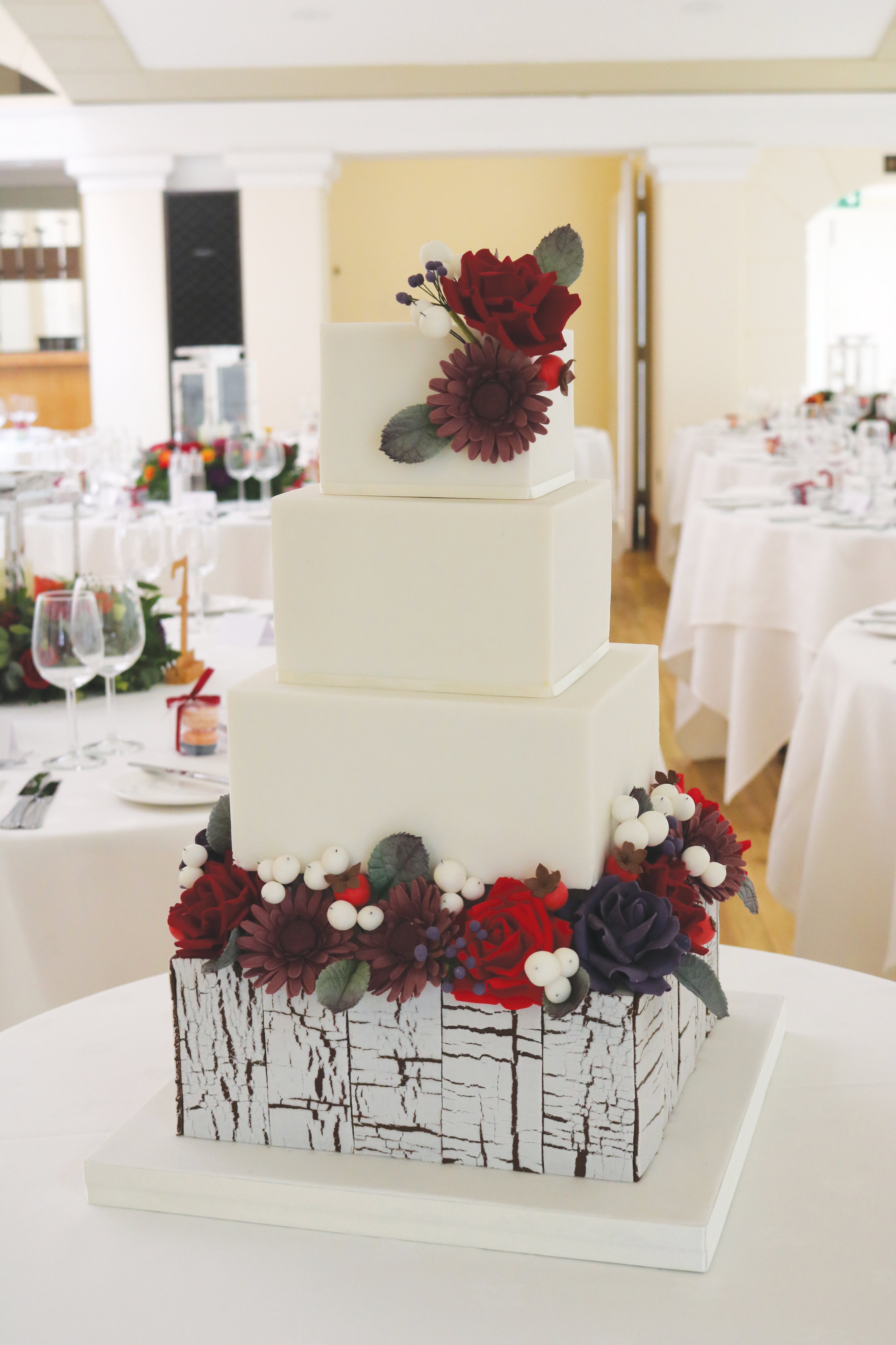 A wedding cake with painted distressed wood effect tier with sugar flowers