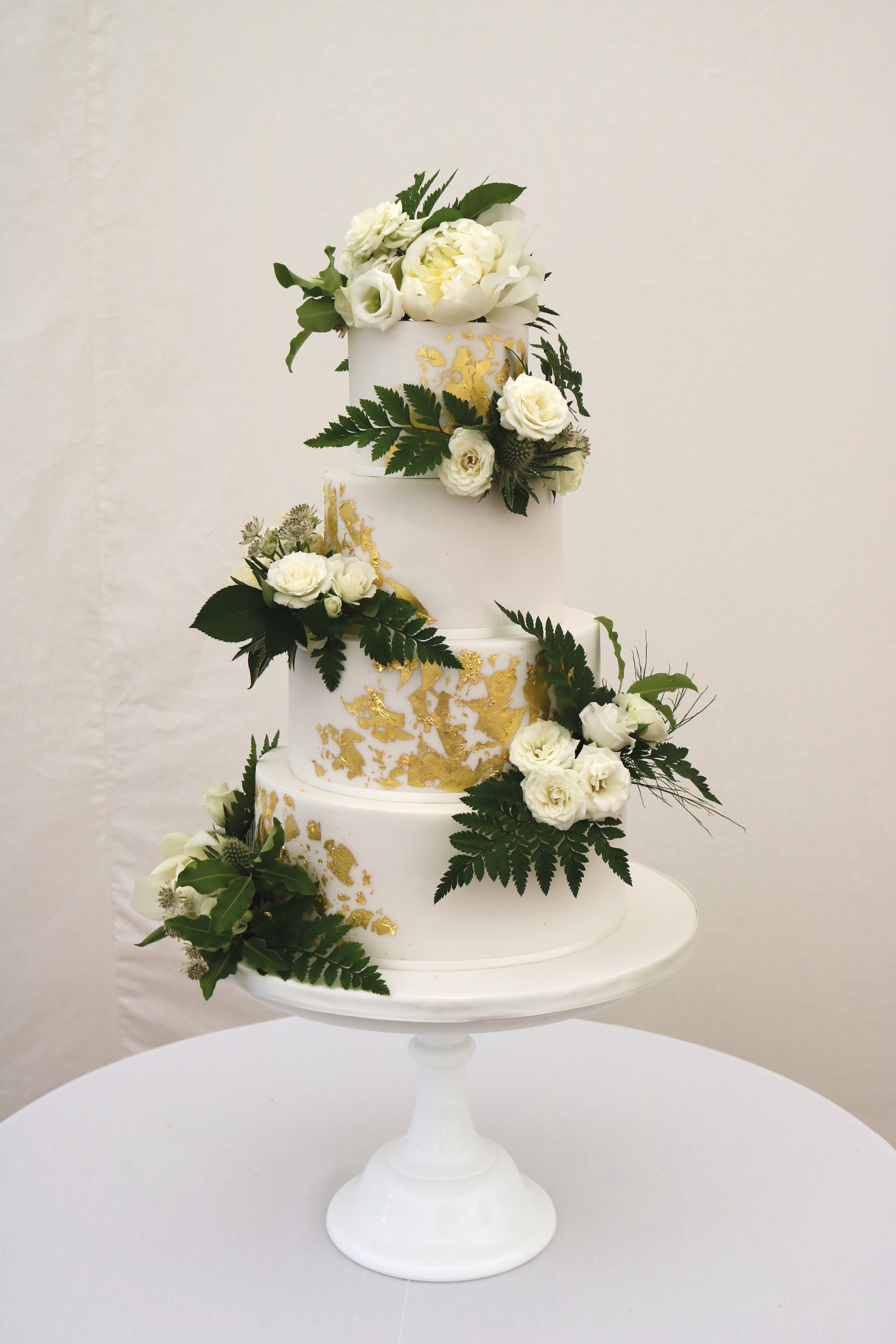 Cake with gold leaf flakes and fresh green and white flowers
