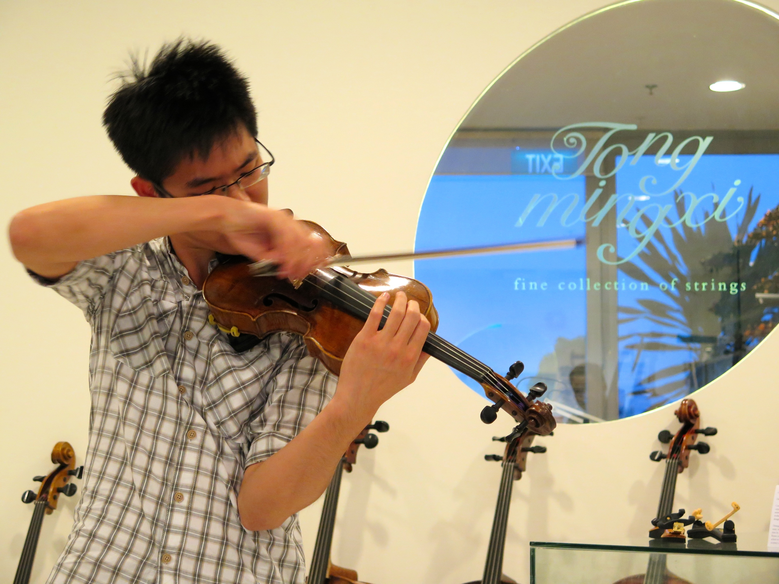 Violinist Alan Choo playing on one of the violins on display