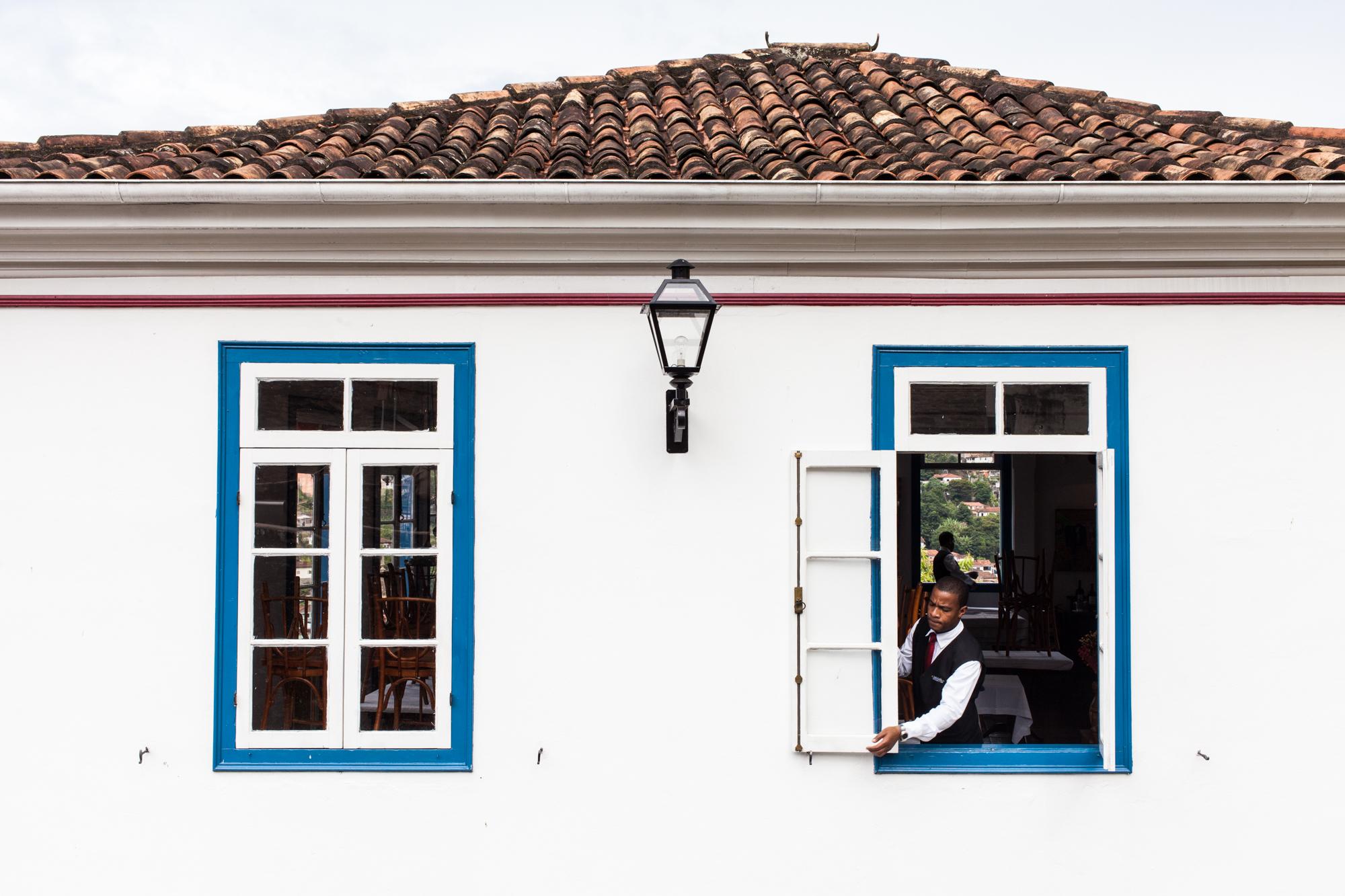 A man closes a restaurant window in Ouro Preto, Minas Gerais