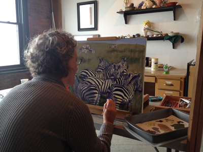 A student works on an oil painting at Lacey's studio.