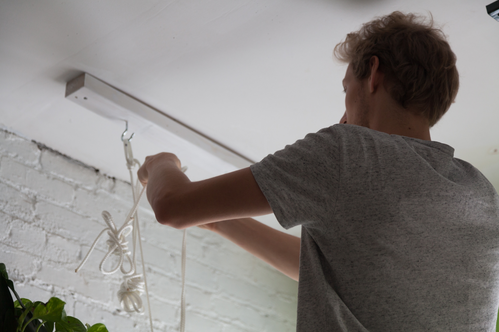 Once the wood in the ceiling was painted, Sander began to loop the rope.