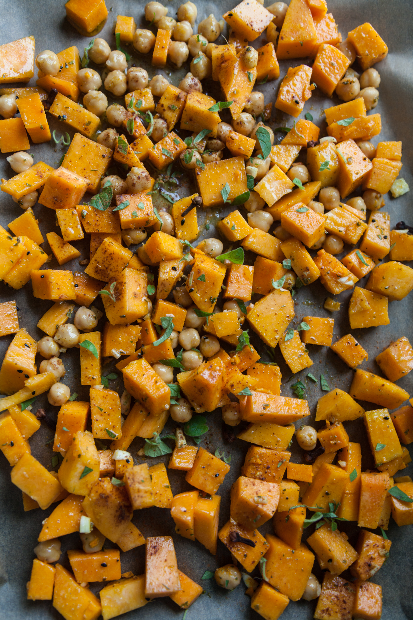 Toss the butternut squash and chickpeas with olive oil, cinnamon, salt,  nigella, and homegrown oregano.