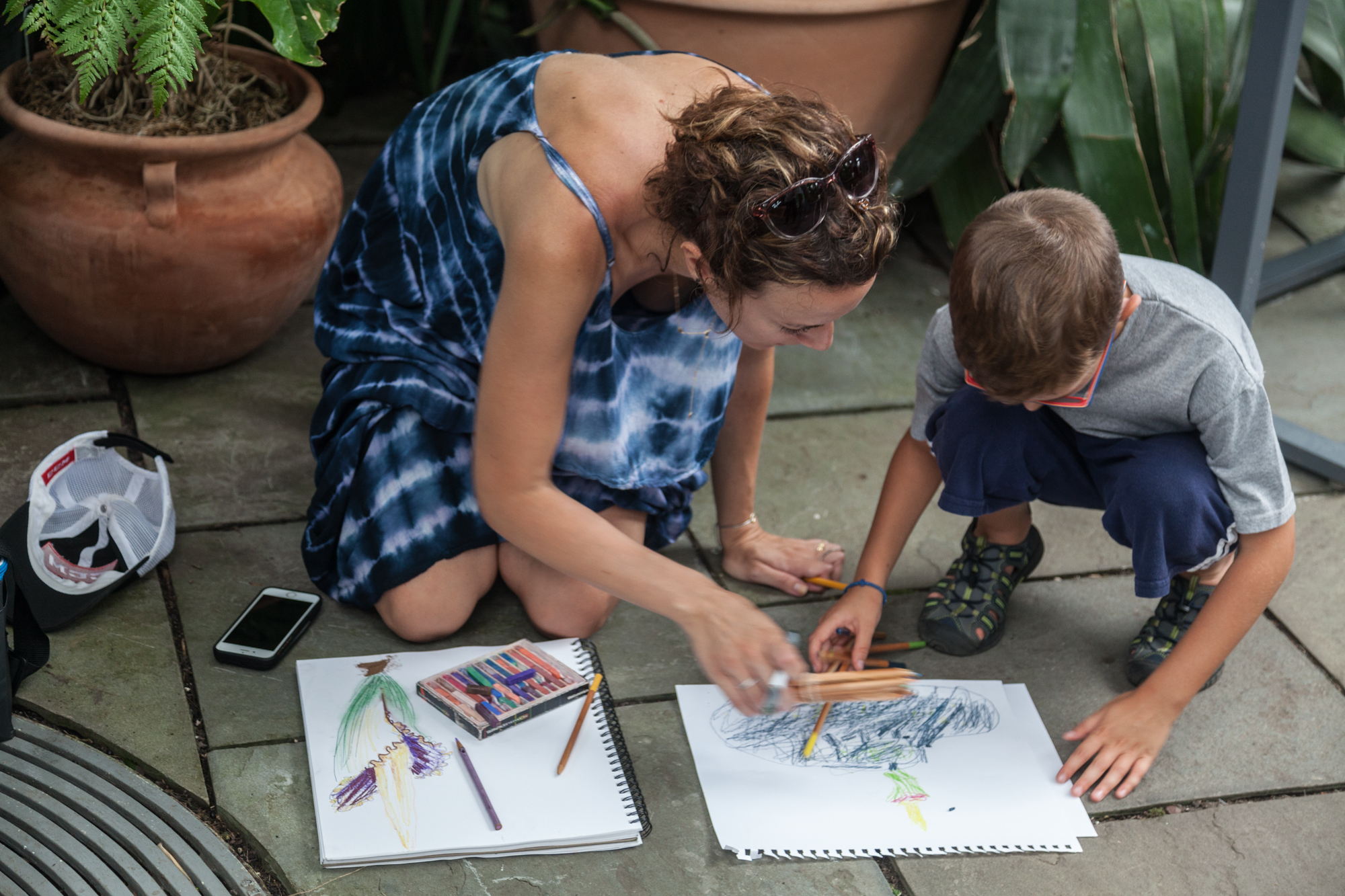 A mother and son do their best artistic inspiration of the corpse flower ( Amorphophallus titanum ) in bloom, memorializing the moment in colored pencils and pastels.