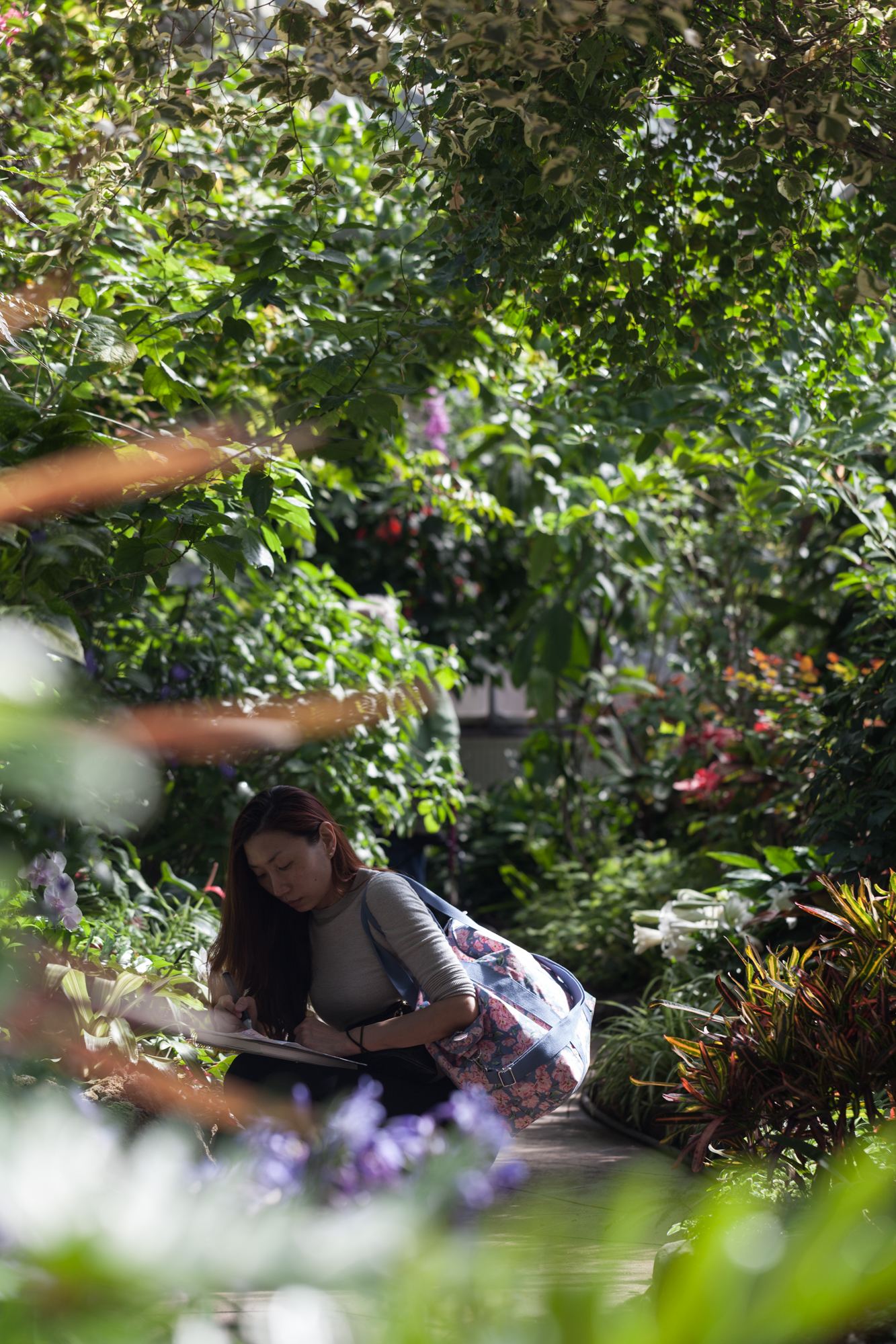 A young woman takes notes of different specimens at the Allan Garden Conservatory in Toronto.