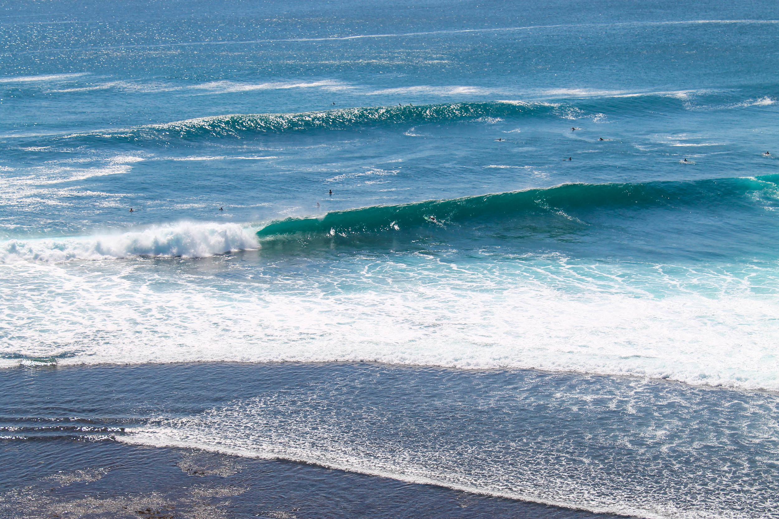 Surfers over Uluwatu cliff.
