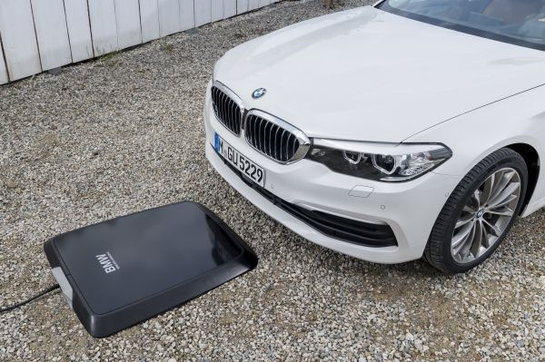 The BMW BMW 530e iPerformance pulling up to an induction charger