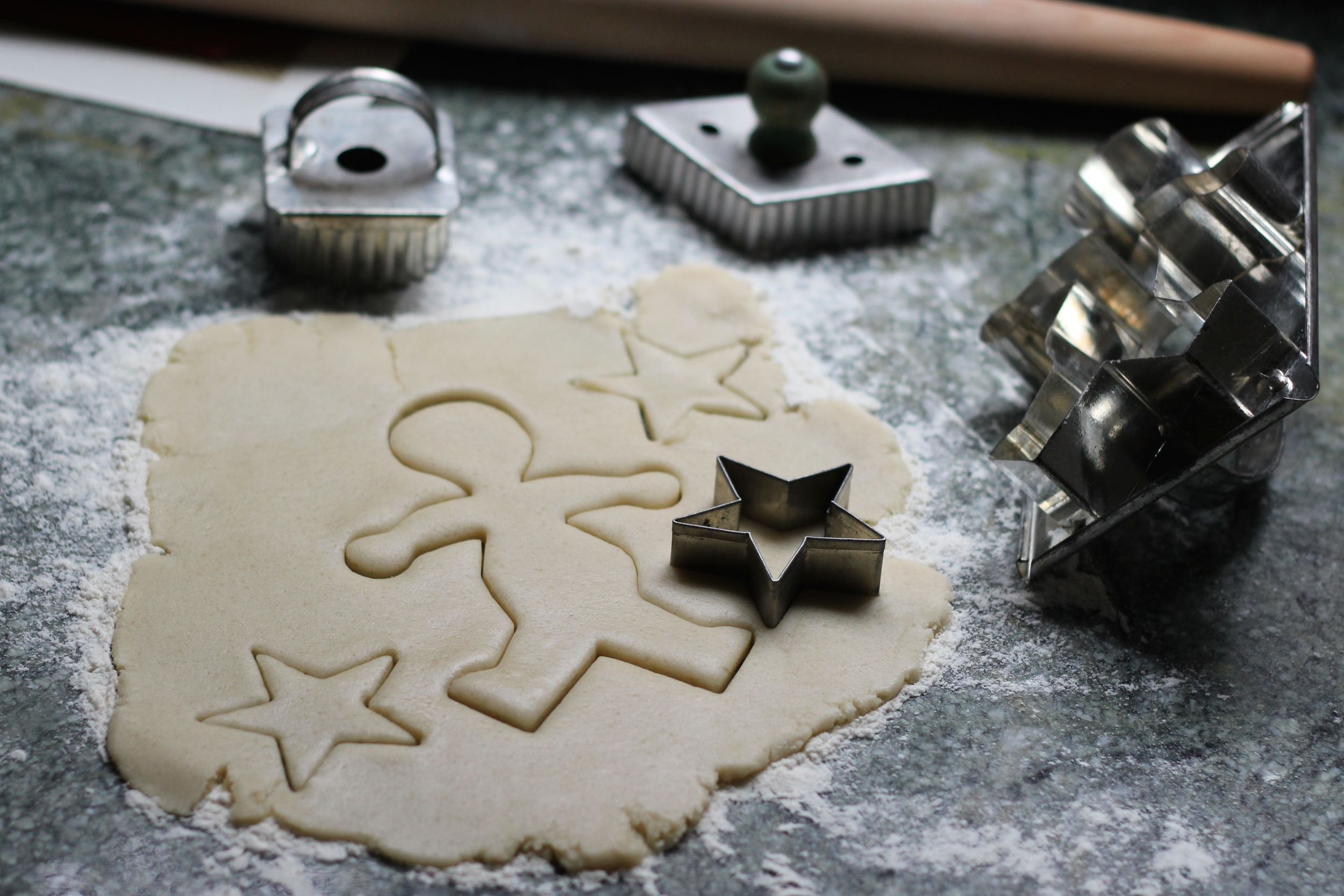 A floured work surface with rolled out butter cookie dough. A great recipe for holiday cookies, or whatever shape cookie cutters you have at your house.Recipe at ThreadandWhisk.com.