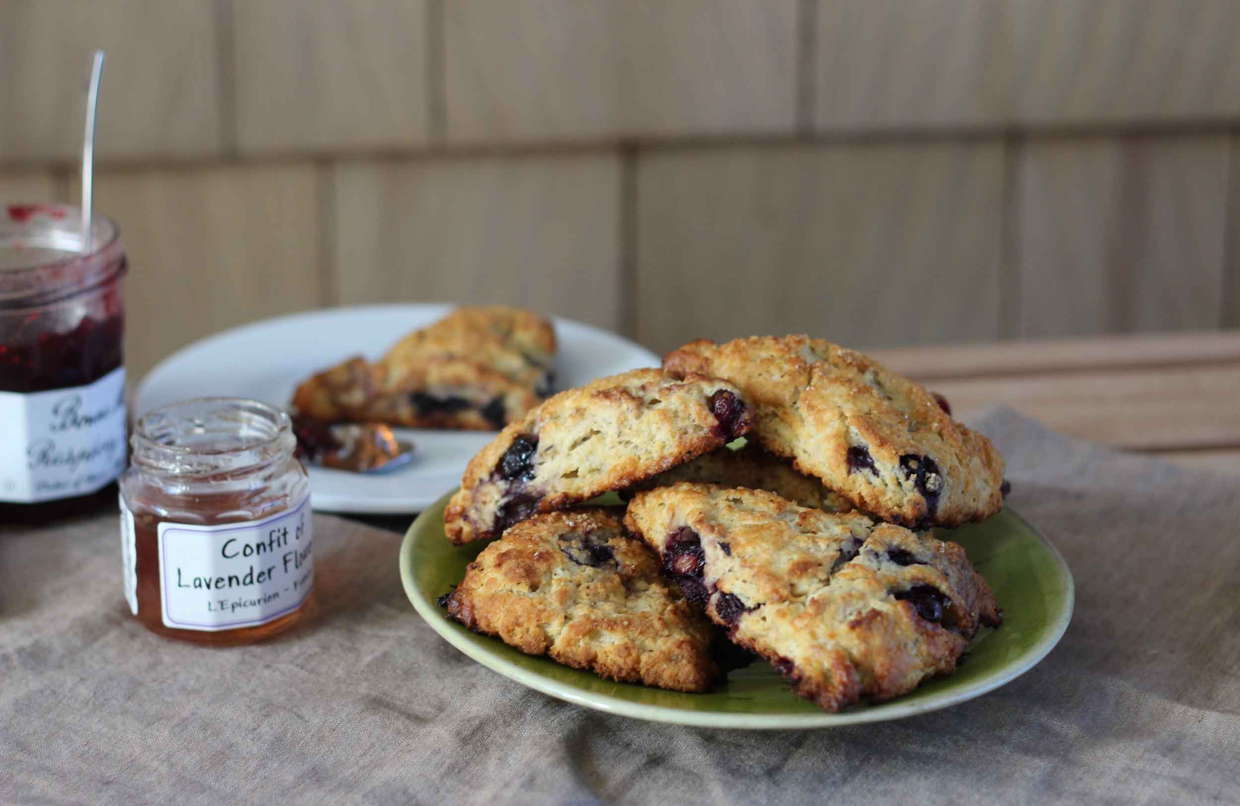 A freshly baked plate of blueberry lavender scones, with some jams waiting to be slathered on them. Scone recipe at ThreadandWhisk.com.