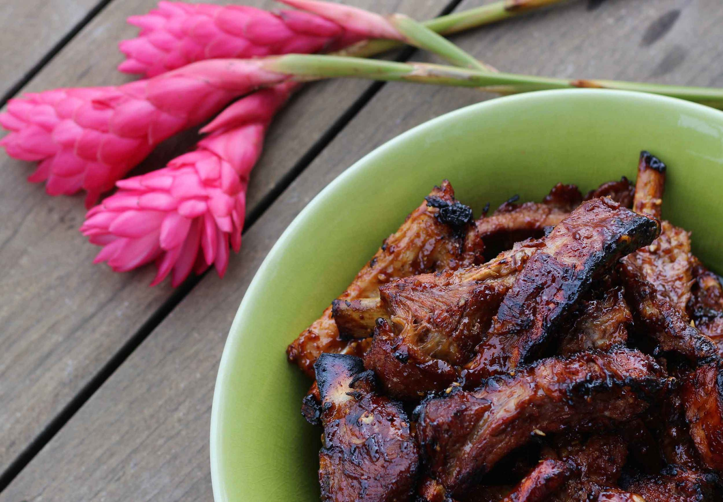 A ready-to-eat platter of barbeque ribs sits next to some tropical pink flowers. Learn how to make delicious but easy ribs. Recipe at Threadandwhisk.com.