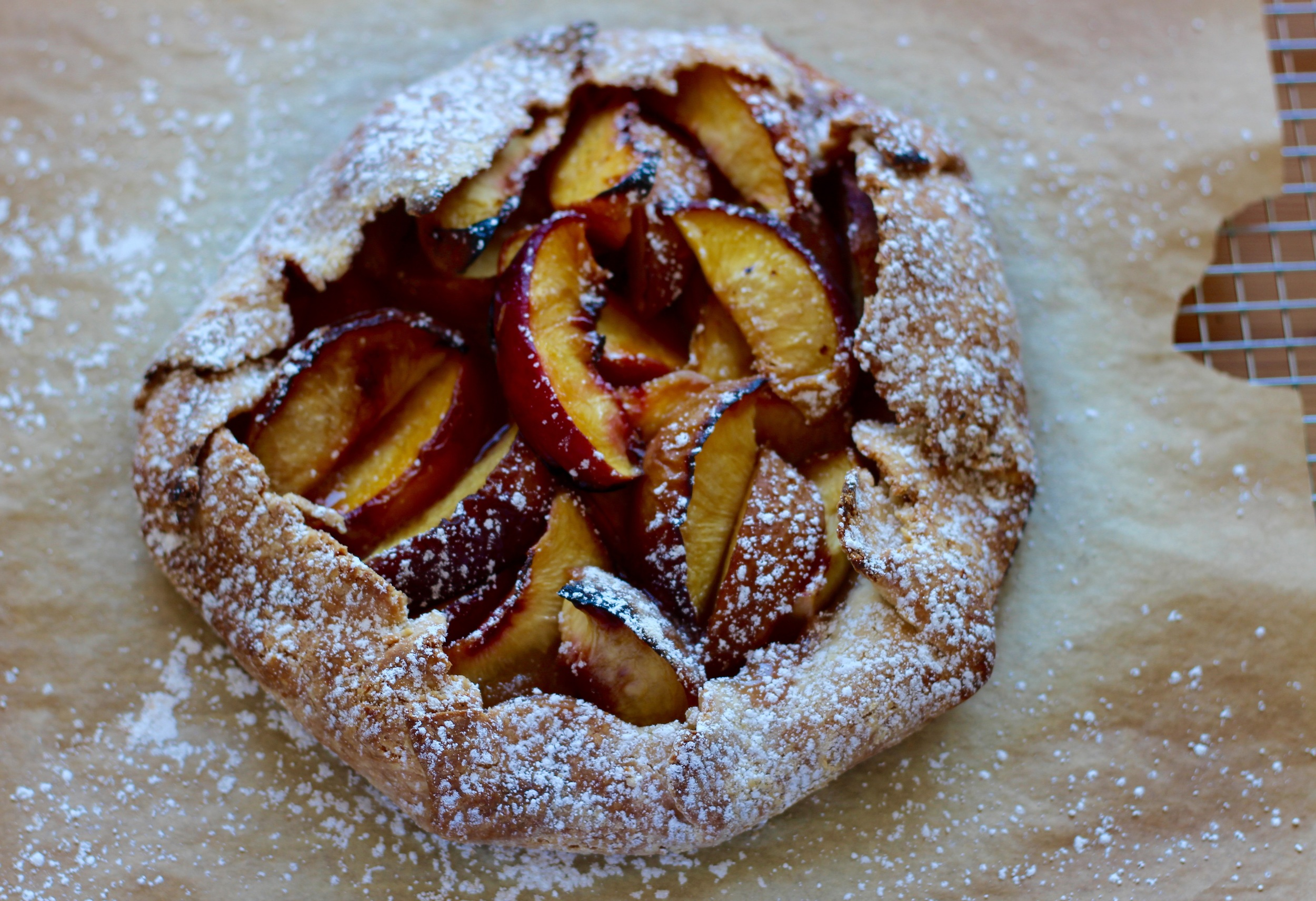 Our just-from-the-oven peach crostata is freshly dusted with powdered sugar. This recipe is great with apricots, berries, and plums too! Recipe at ThreadandWhisk.com.
