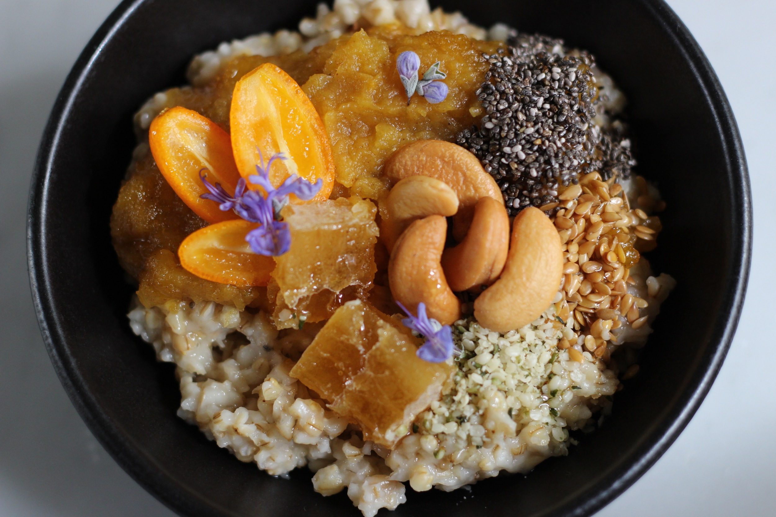 A complex and delicious bowl of oatmeal with pumpkin, cashews, kumquats, chia seeds, and chunks of comb honey. Garnished with edible flowers. Recipe at ThreadandWhisk.com.