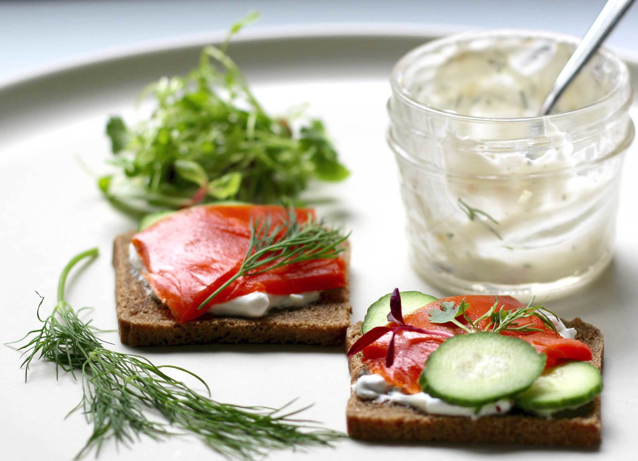 Making salmon, cucumber canapes with dill and creme fraiche