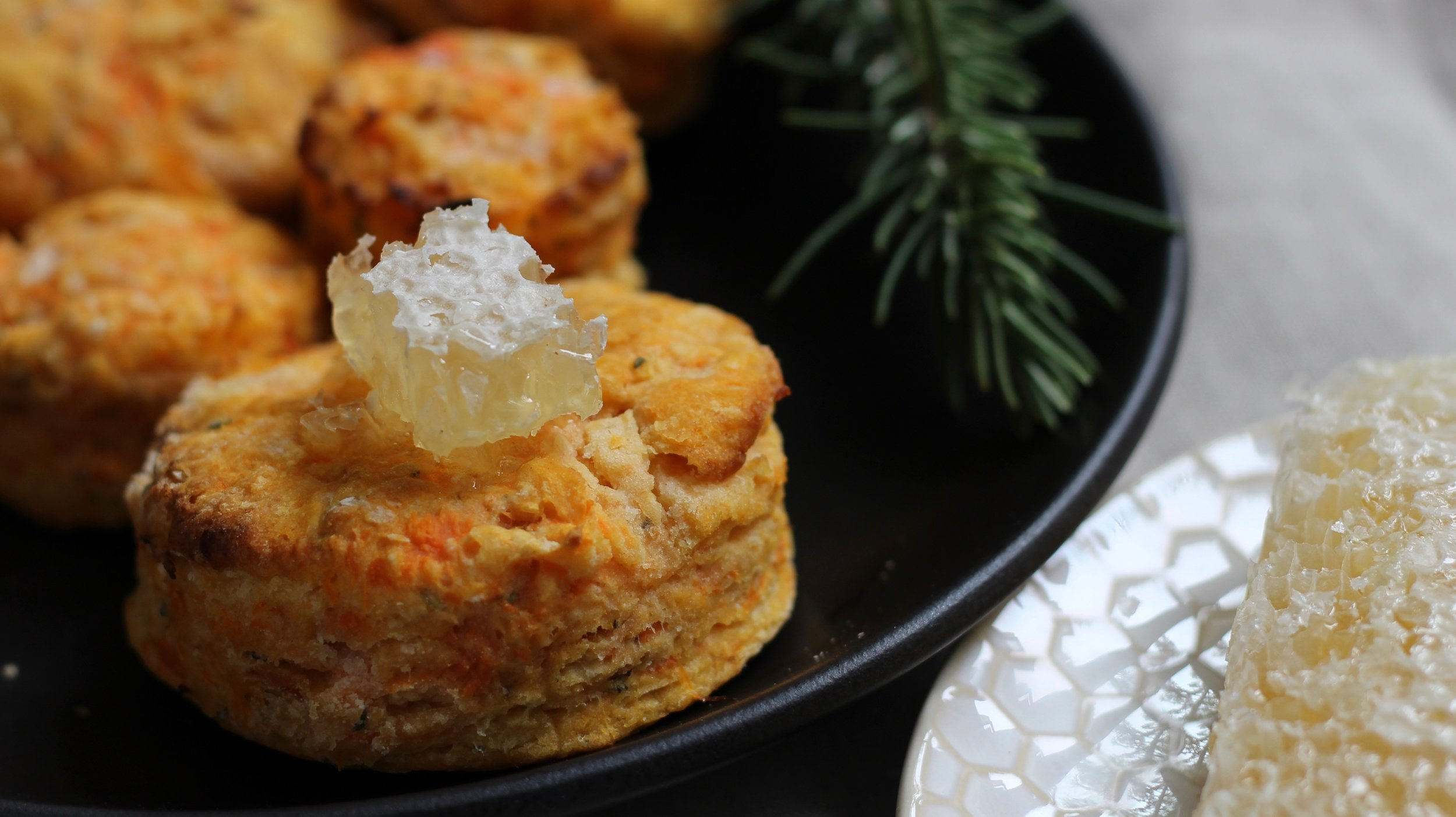 A plate of warm sweet potato and rosemary biscuits with a generous chunk of comb honey melting on top.