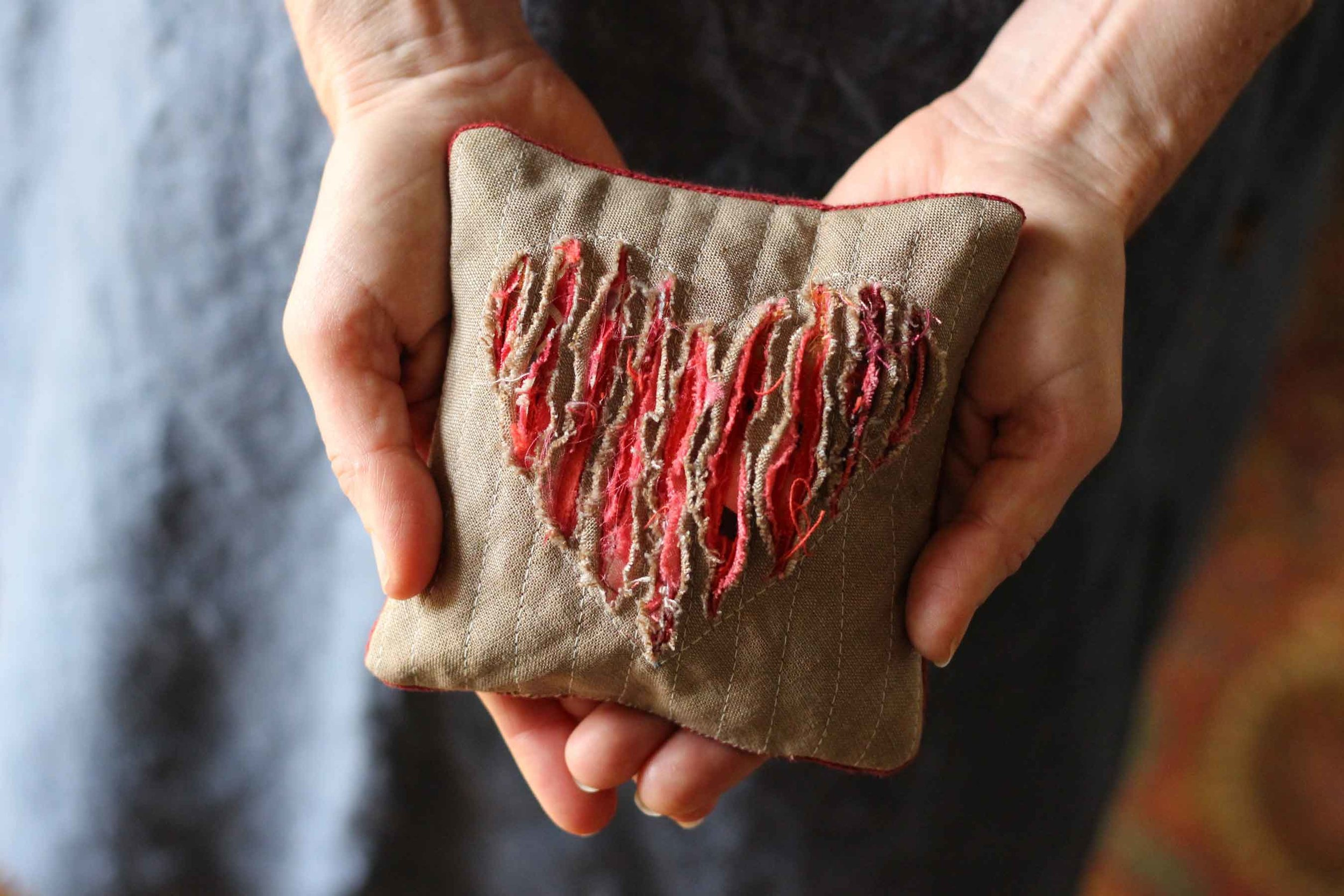 Warming our hands with our rice filled pillow. The heart design is made with a technique called slashing. This is a great project for using up scraps of fabric. Find the instructions at Thread & Whisk.com