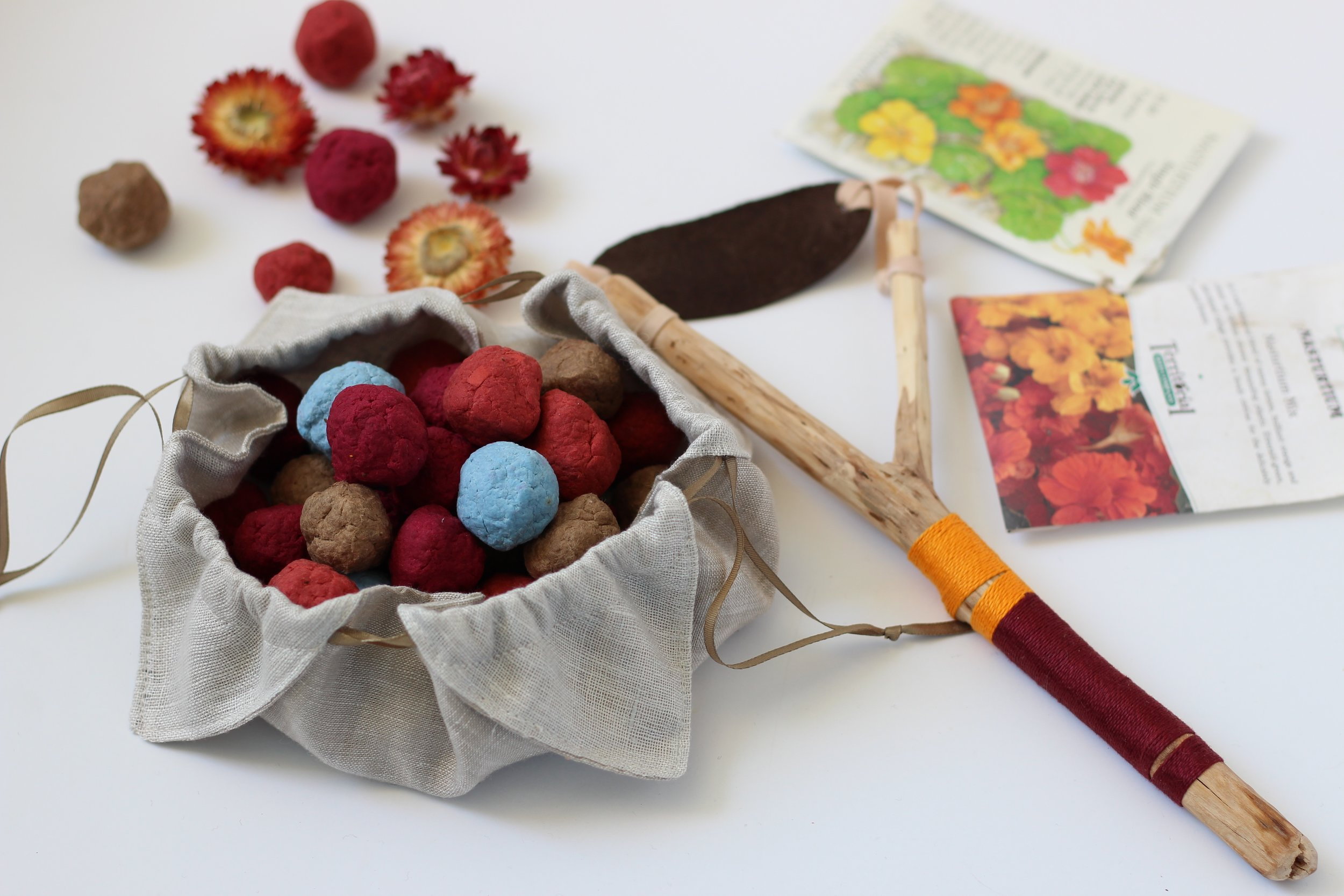 A homemade slingshot waits to be used to send our wildflower seedballs out into the field to spread some flower joy. Handmade Paper Seed Pebbles are fun to make, and even more fun to give as a gift. What a conversation starter!