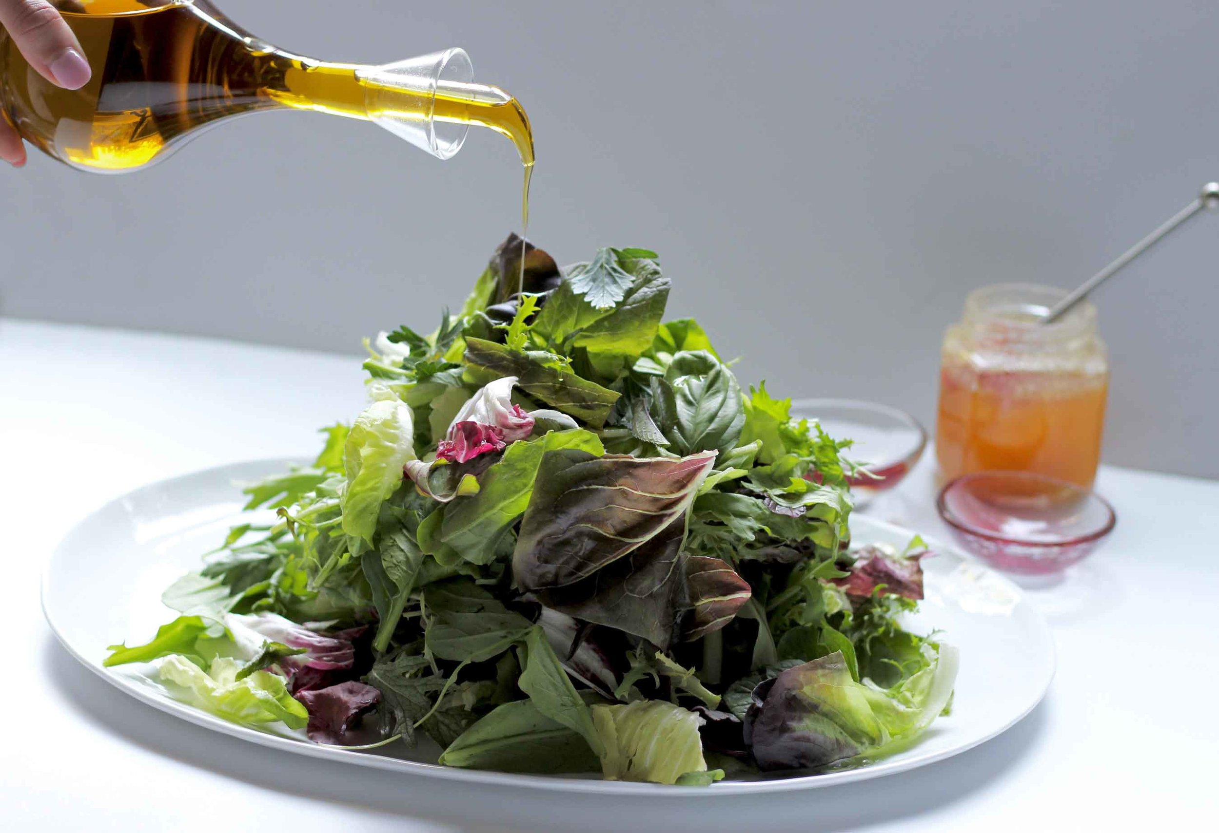 Pouring our best olive oil on a salad of red butter lettuce, treviso, and little gems with fresh basil, mint and cilantro.