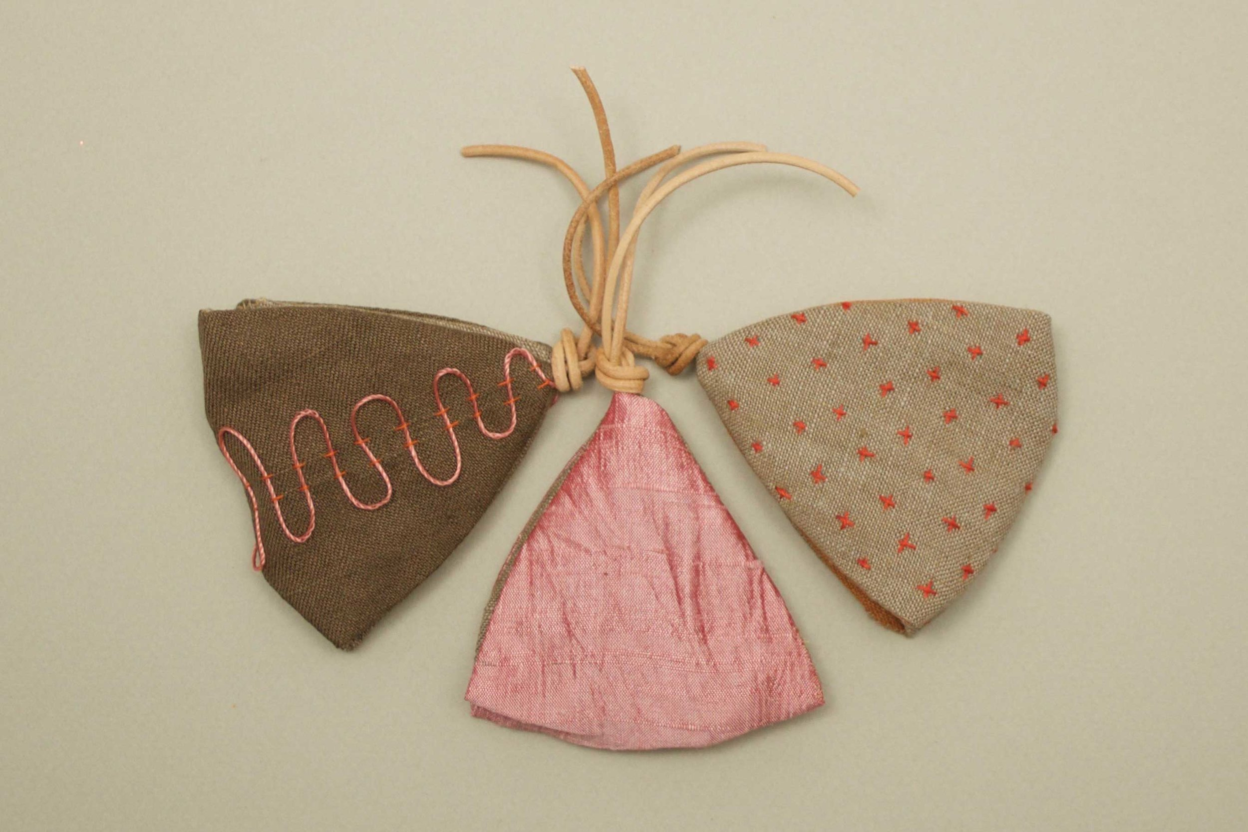 3 little pocket sized sachets handmade with silk and linen, hand embroidered for a personal touch. The sachet scent is a special holiday blend by Thread & Whisk.