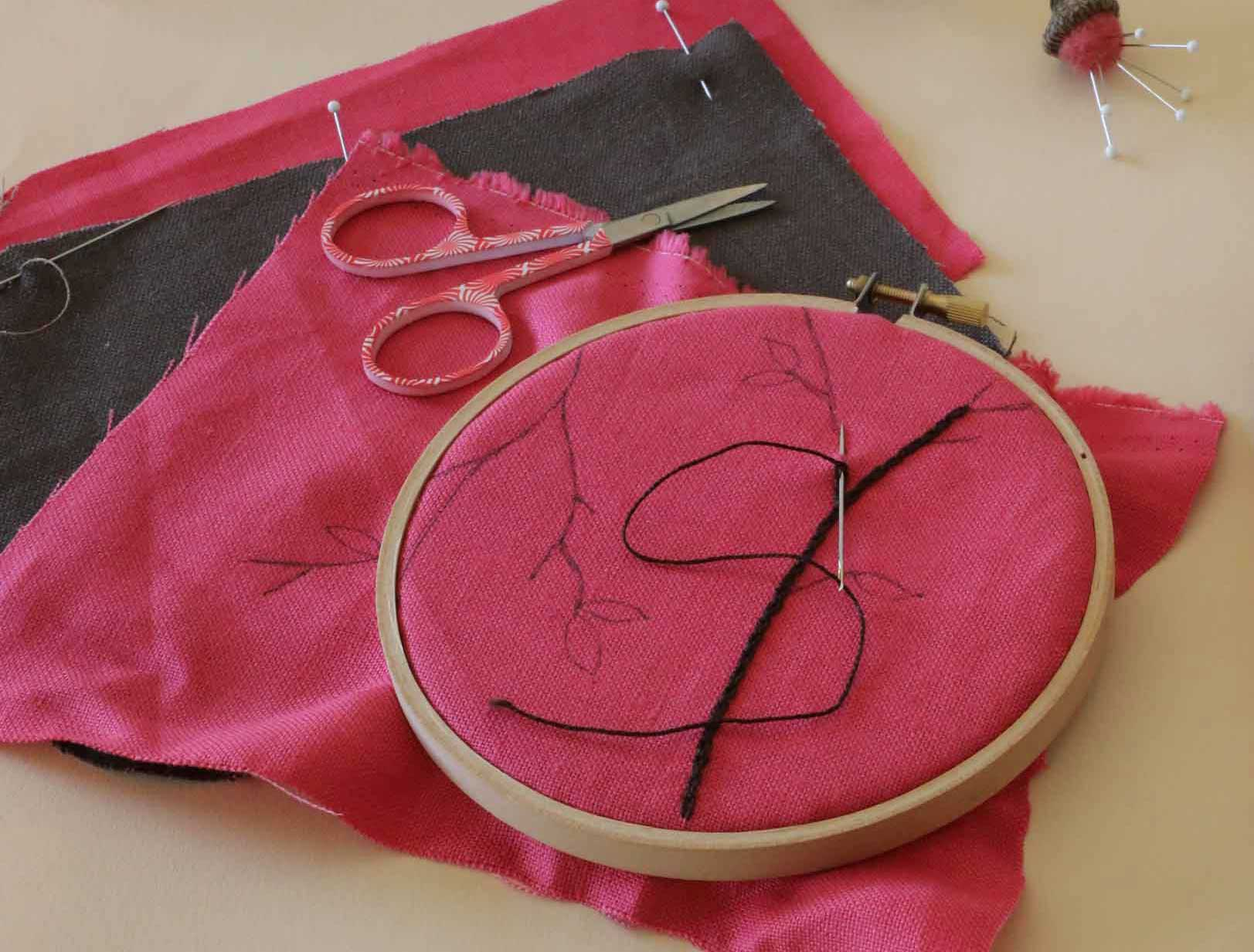 Starting a cheerful embroidery project of flower blossoms on pink linen. We have the design sketched in and the embroidery hoop ready to go.