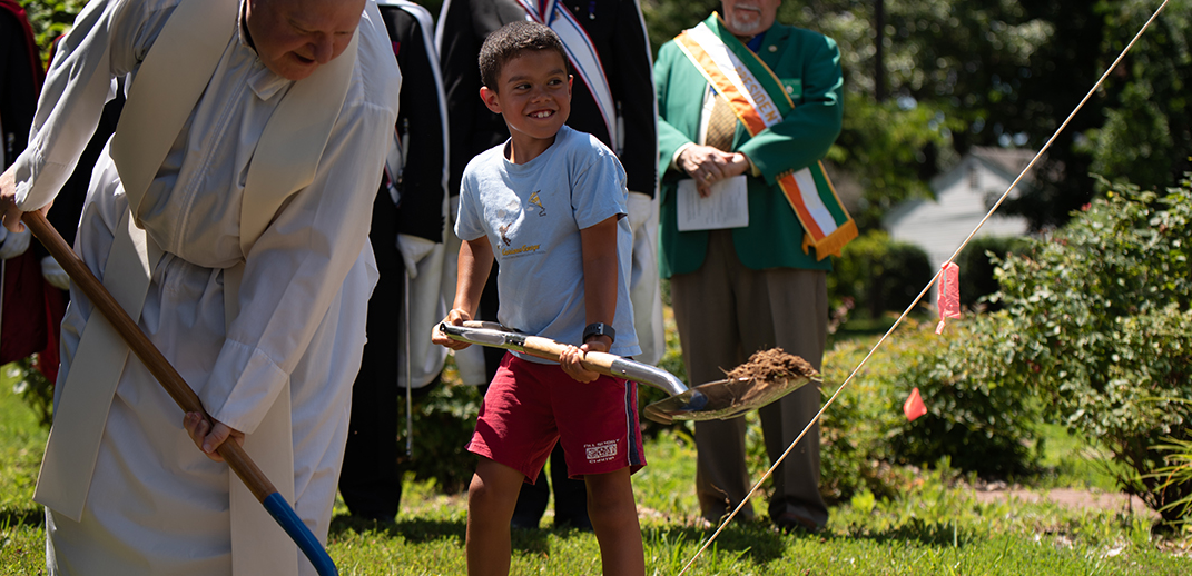 Fr. James S. Barkett, pastor of St. Mary of Sorrows in Fairfax, is helped by Luke Havasy at the groundbreaking ceremony June 30. GEORGE GOSS | CATHOLIC HERALD