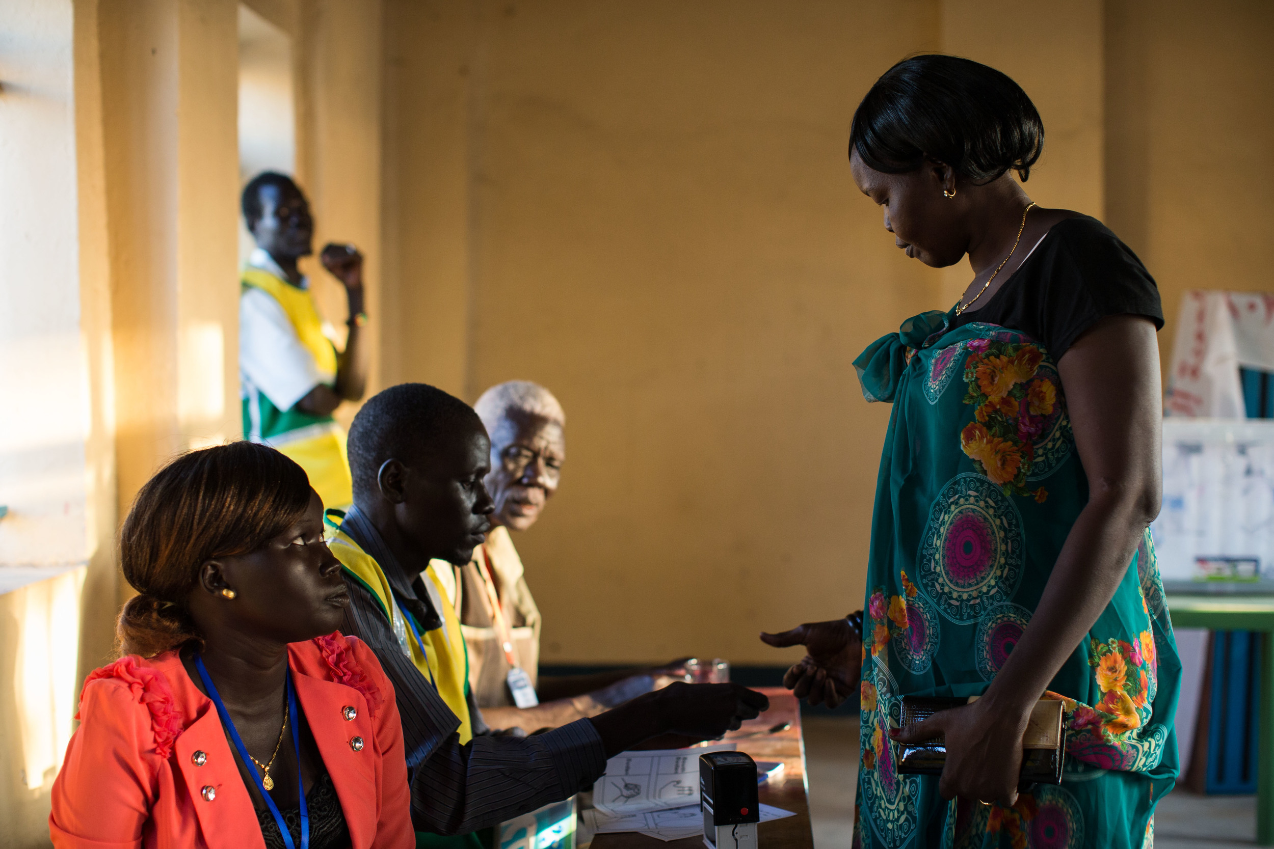A woman receives her ballot from a volunteer for the Abyei Area Community Referendum Commission (AACRC)  at a voting center in Abyei.