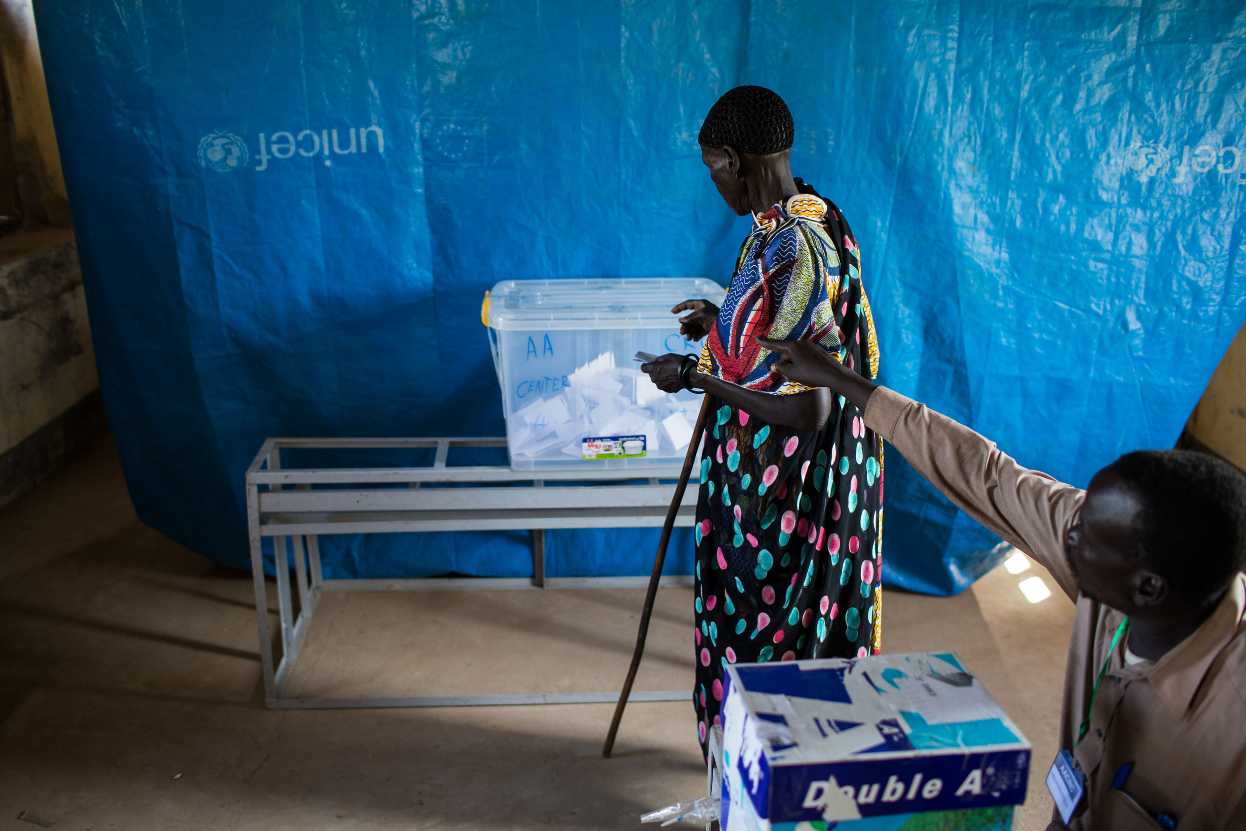 A volunteer with the AACRC directs a woman where to cast her vote at a voting centerin Abyei.
