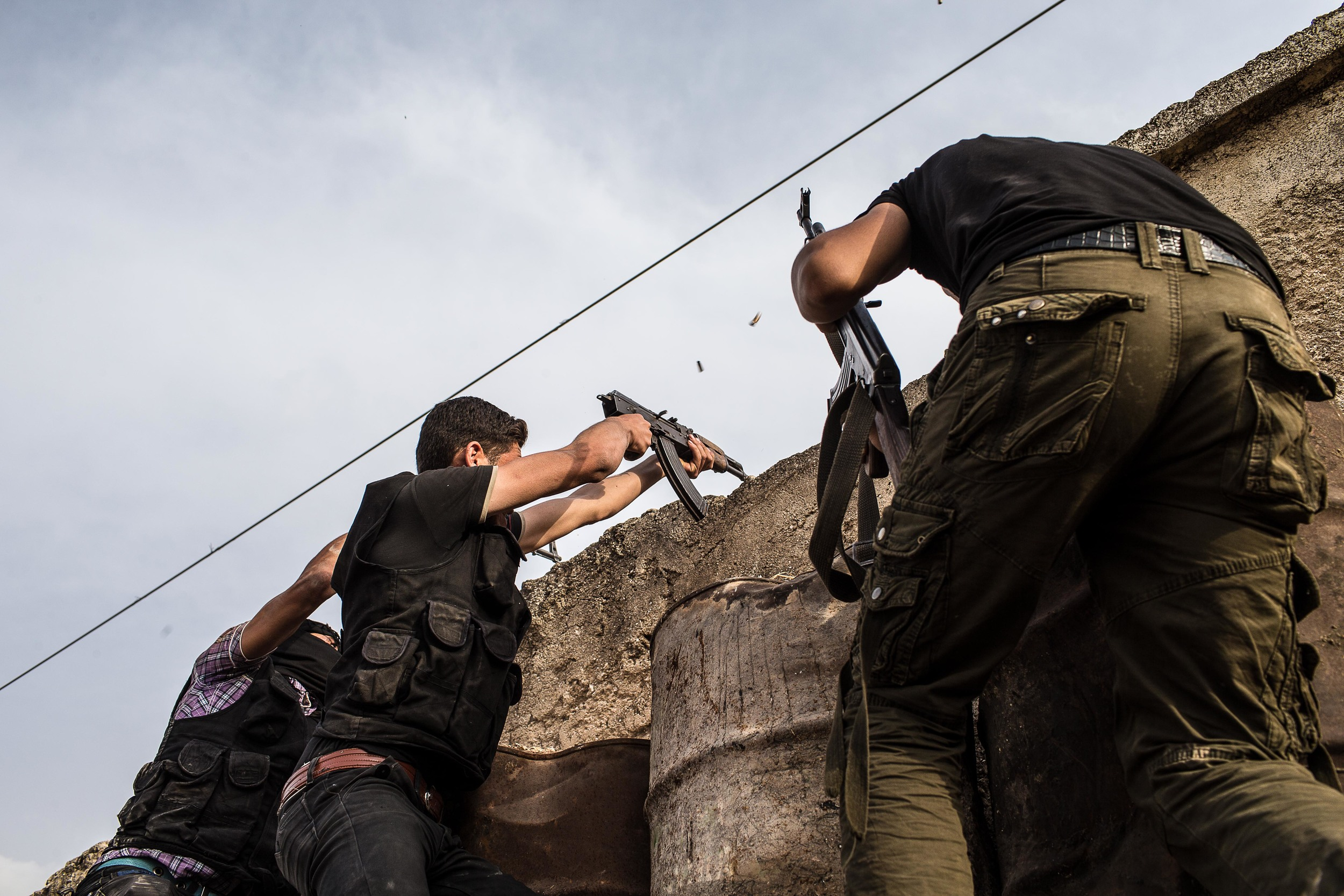 Fighters trade shots with regime soldiers across the wall.