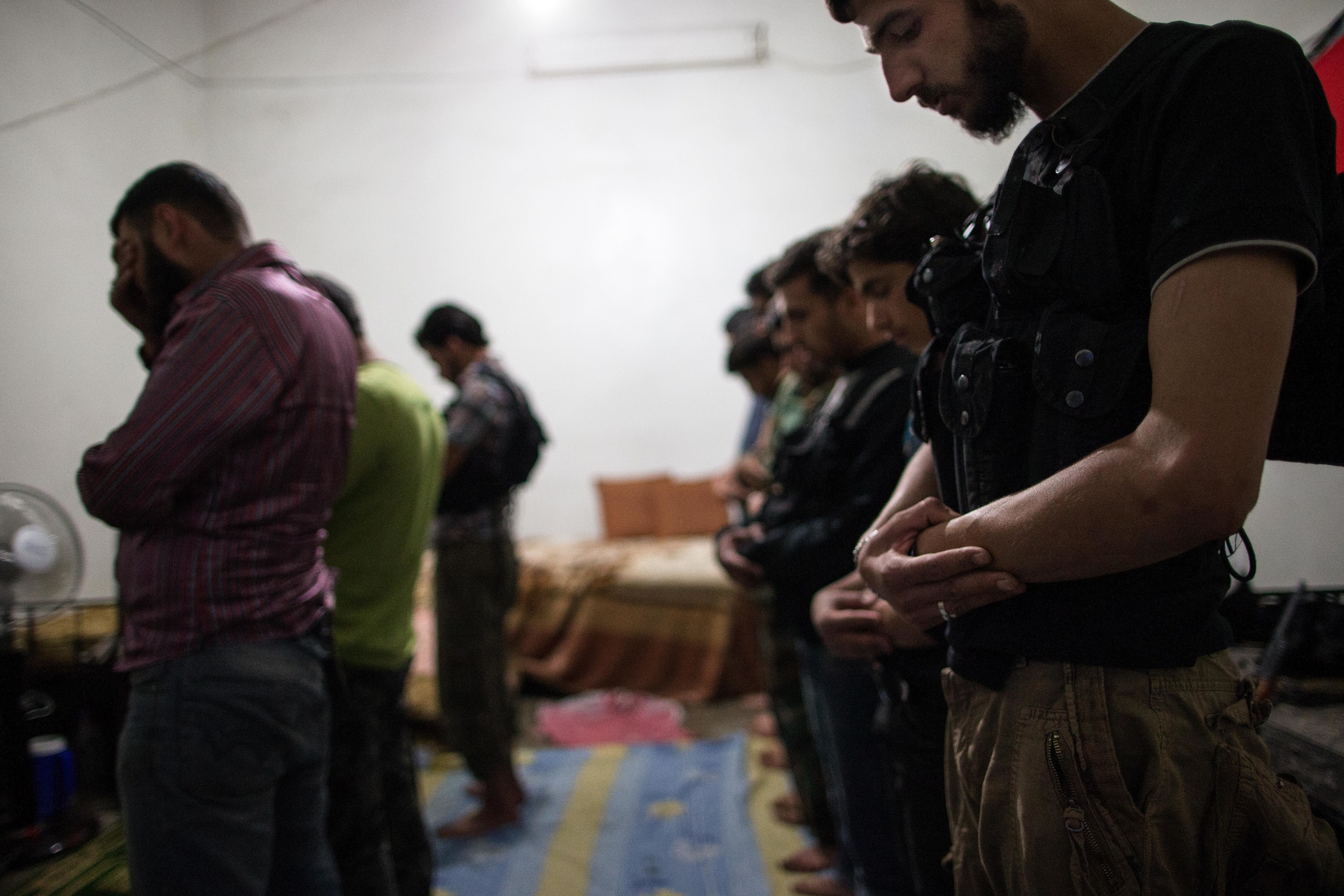 "The battalion performs evening prayer in their base's main room. ""We are moderates,"" says Abu Abdo, ""extremists like Jabhat al-Nusra are a small percentage. We are the ones who decide the future."" There is continued fear that sectarian divisions and extremism will prevent international support and plague the country should Assad ever be ousted."