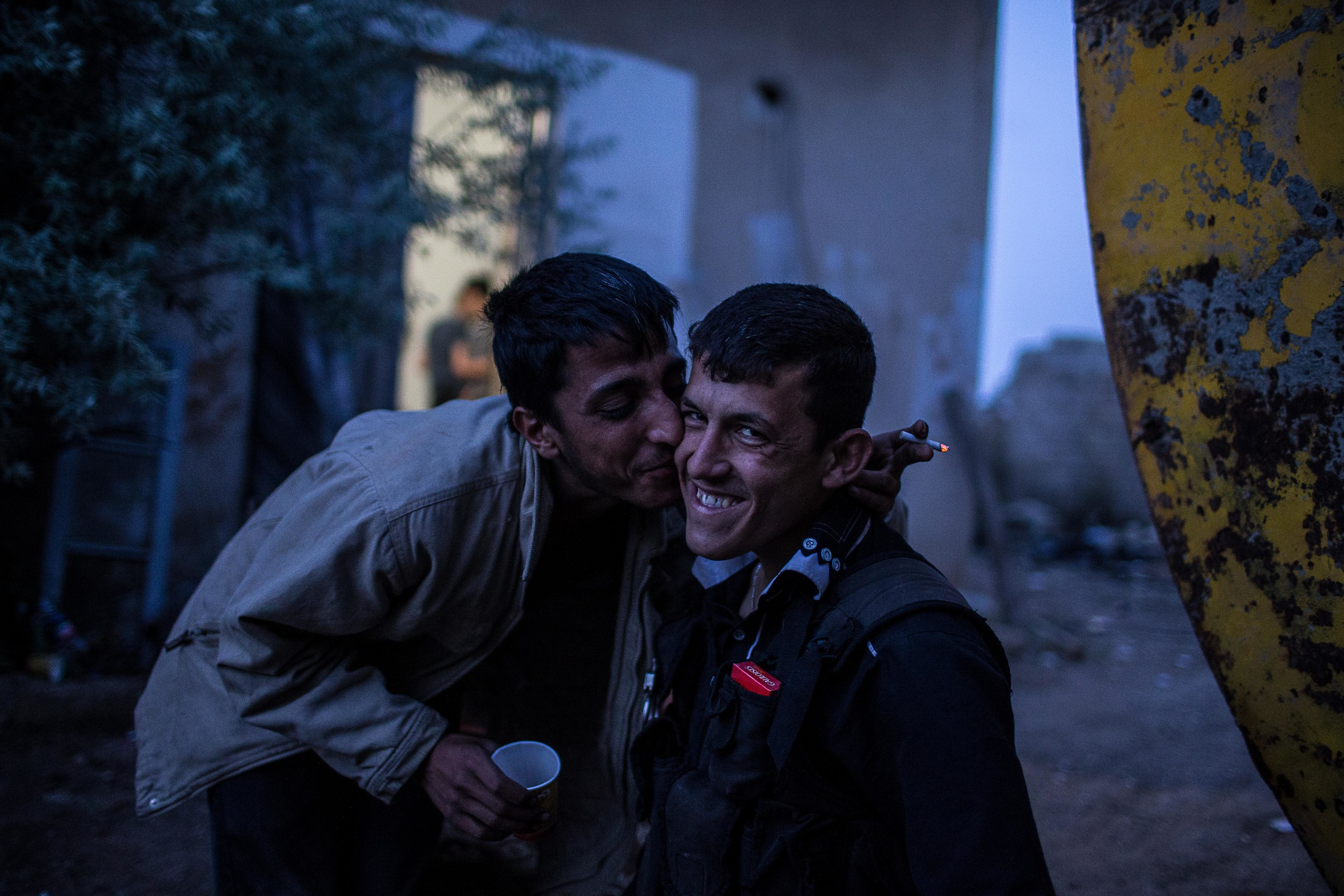 "Hassan, 21 gives Abu Usama, 23 a kiss. Fighters live in extremely close quarters, eating, sleeping, praying, and fighting together for months on end. The phrase ""I love you"" is freely thrown around."