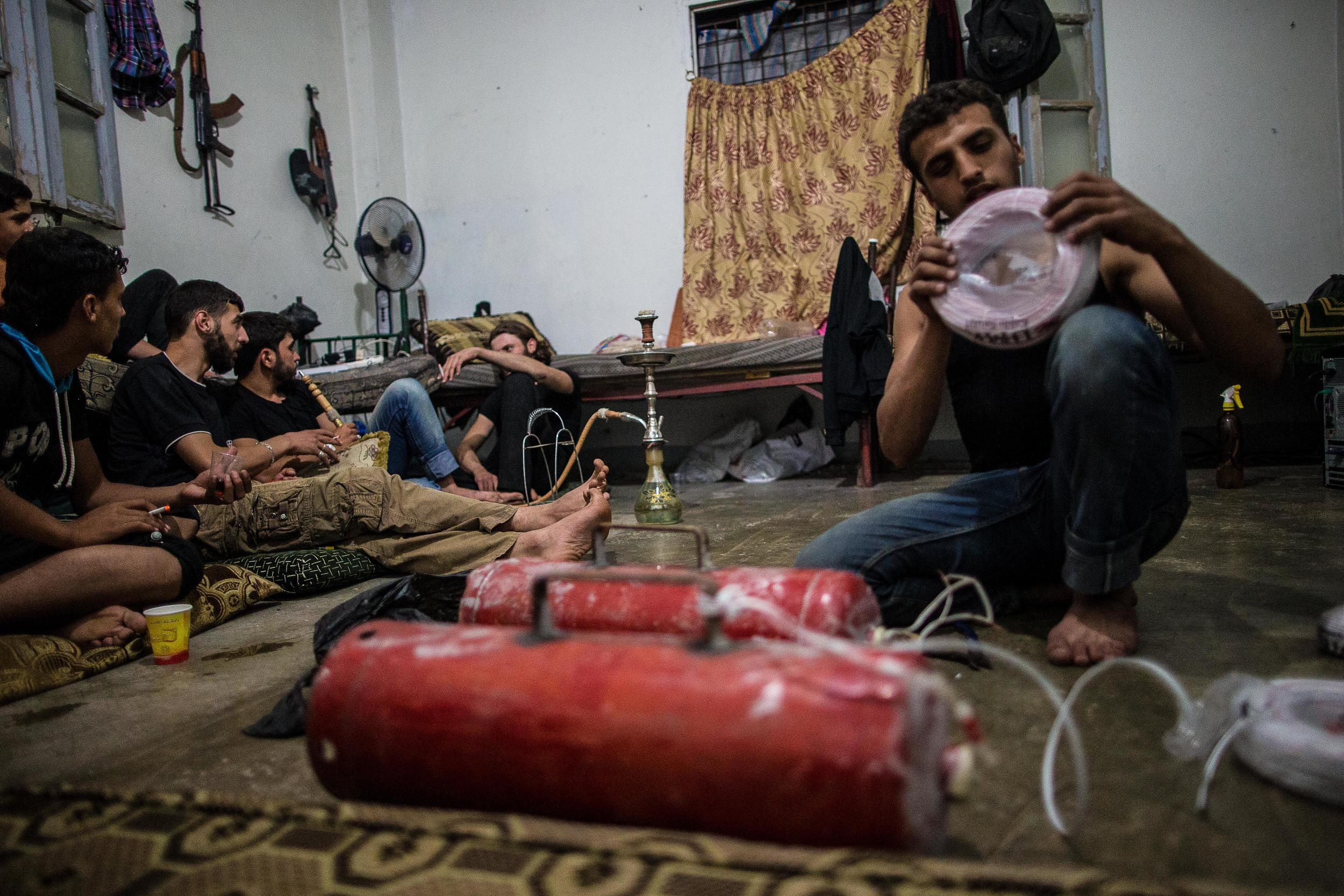 A rebel named Wa'el prepares two homemade explosives the battalion will plant during a night raid in regime-held territory. The battalion occasionally undertakes a small operation under the cover of night, typically to check the position of enemies, steal desperately needed weapons and munitions, and keep regime fighters on defense.
