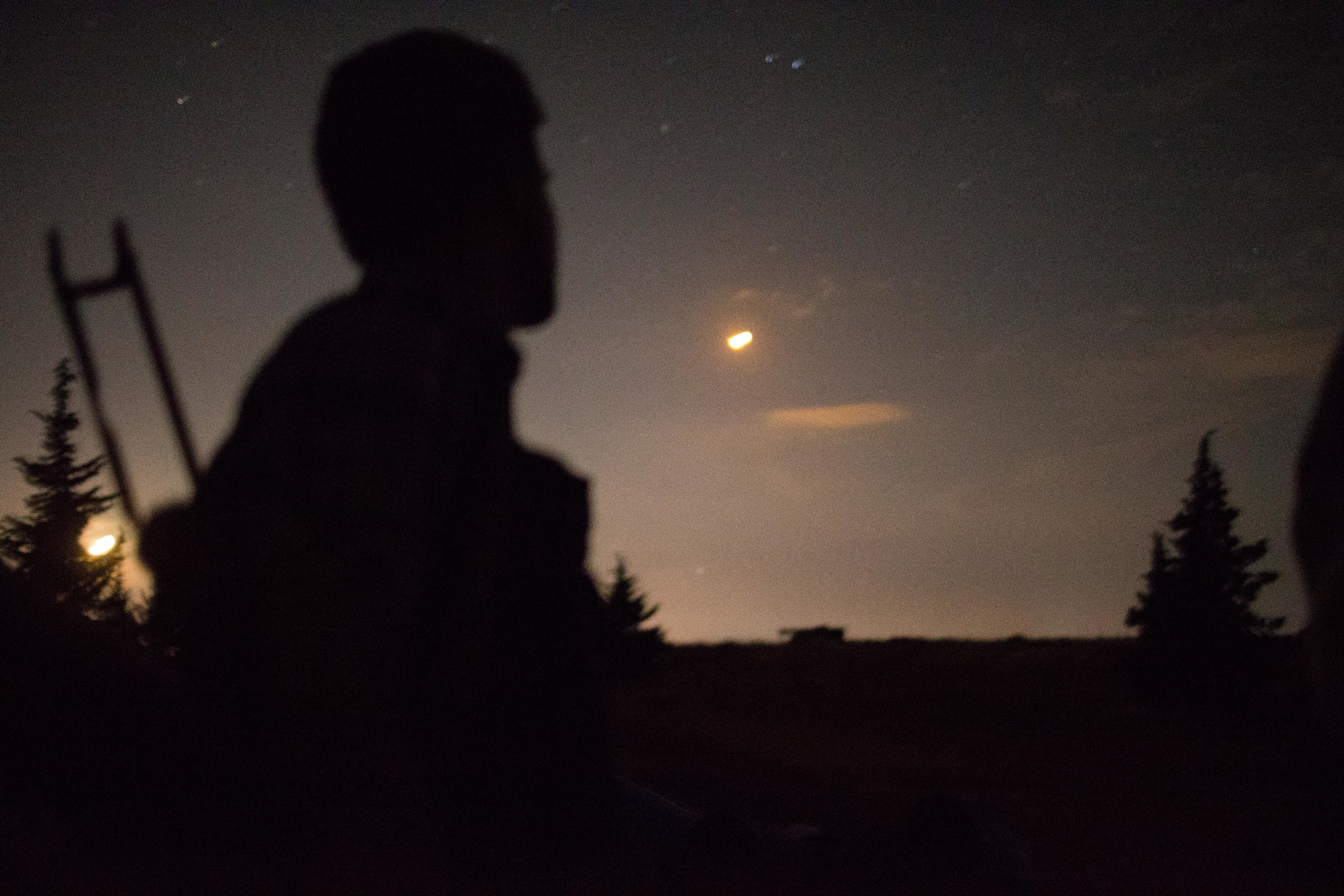 Yaseen watches a tracer blaze across the night sky. Regime MiGs use these flares as guides for nightly bombing runs.