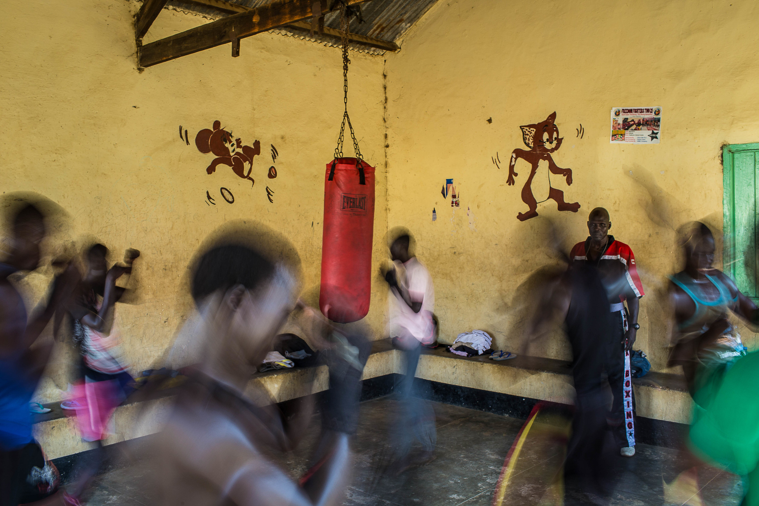 Puro looks on as members of his kickboxing team train at their center in Juba.