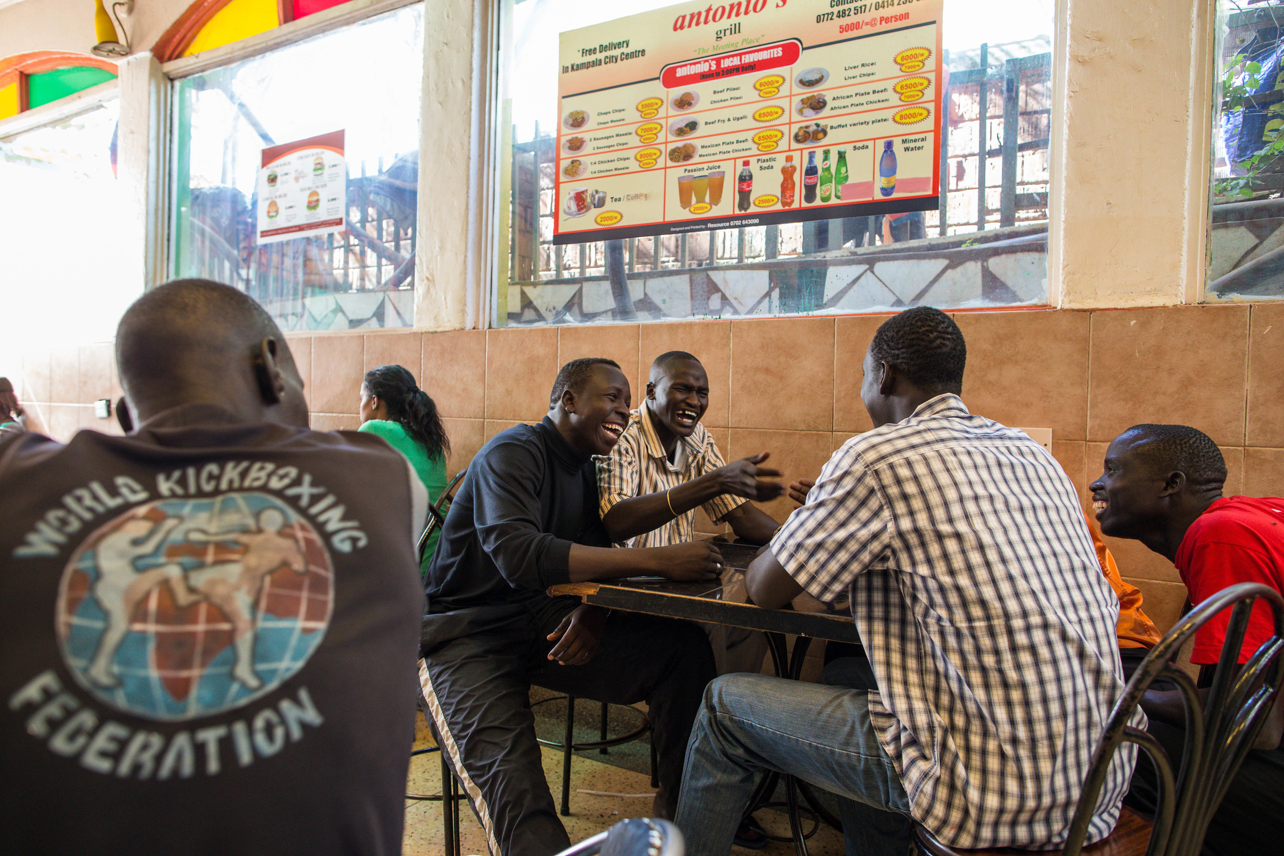 Team members laugh together after finishing lunch at a restaurant in Kampala. Aware that it would be a barrier to competition, Puro makes sure no team member has to pay for anything on the trip.