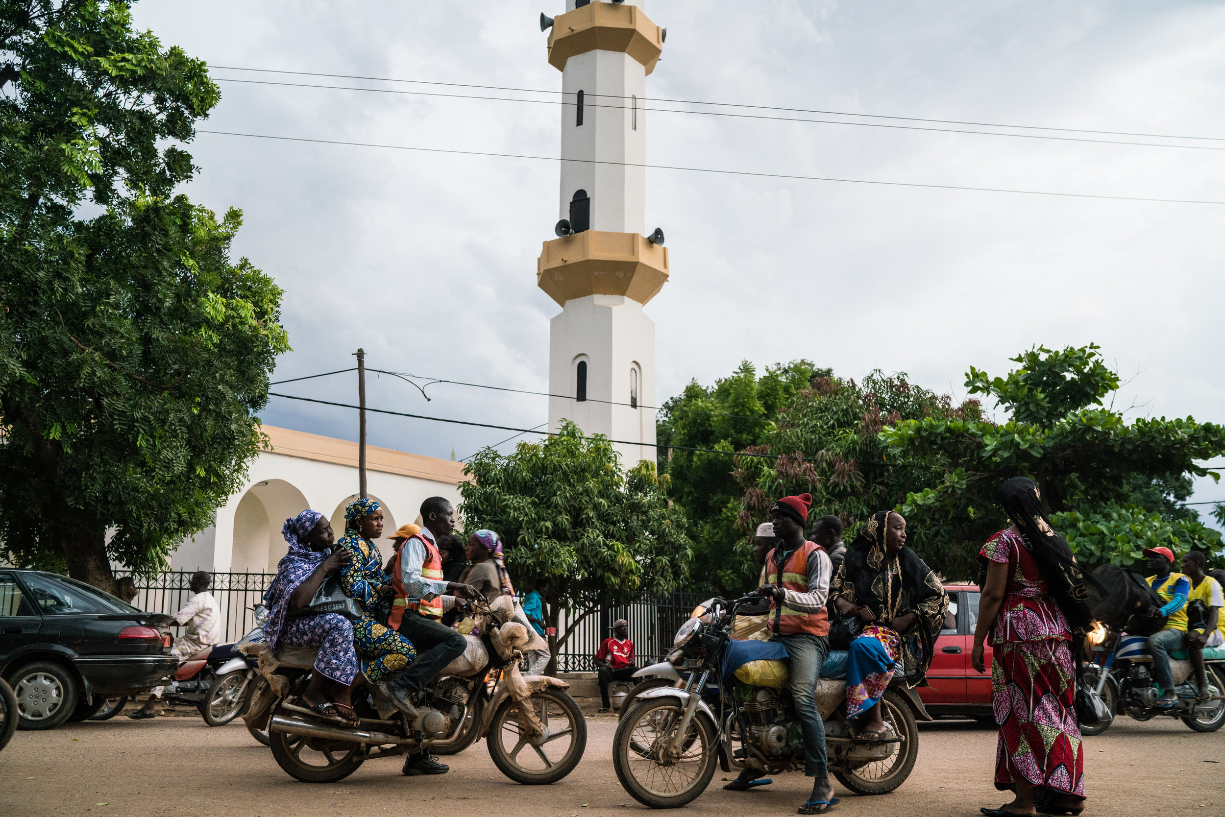 Women climb on board moto-taxis outside a mosque in Garoua, Cameroon.