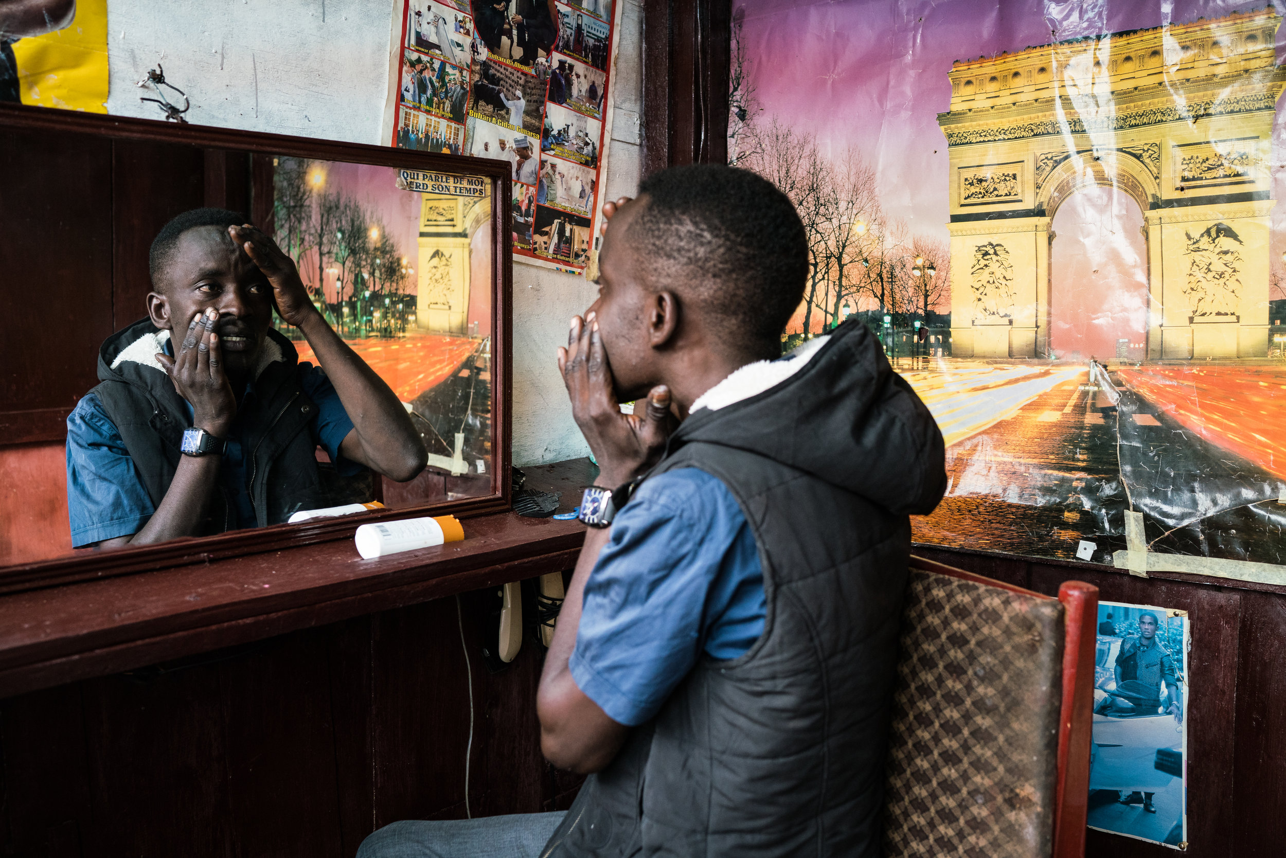 "Oumarou Aziz, 35, pushes on his face as he applies face cream in his barber shop in Ngaounder, Cameroon. Aziz began taking the drug eight years ago, ""It made me very strong,"" says Aziz of the drug's initial effects, but he's had to keep upping the dose. He has overdosed multiple times, but can't stop."