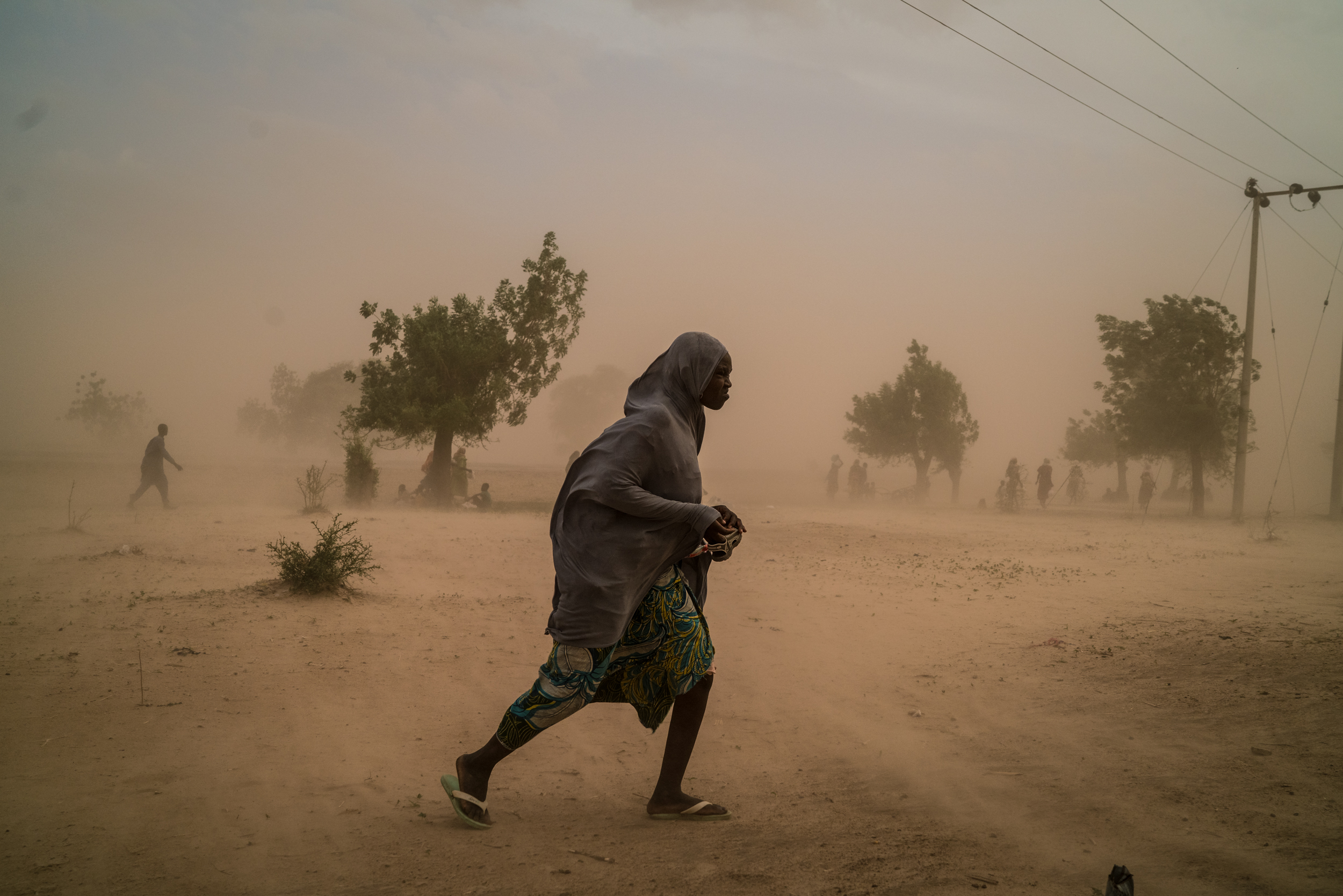 A young displaced woman walks in a dust storm ripping through Maiduguri, Nigeria.
