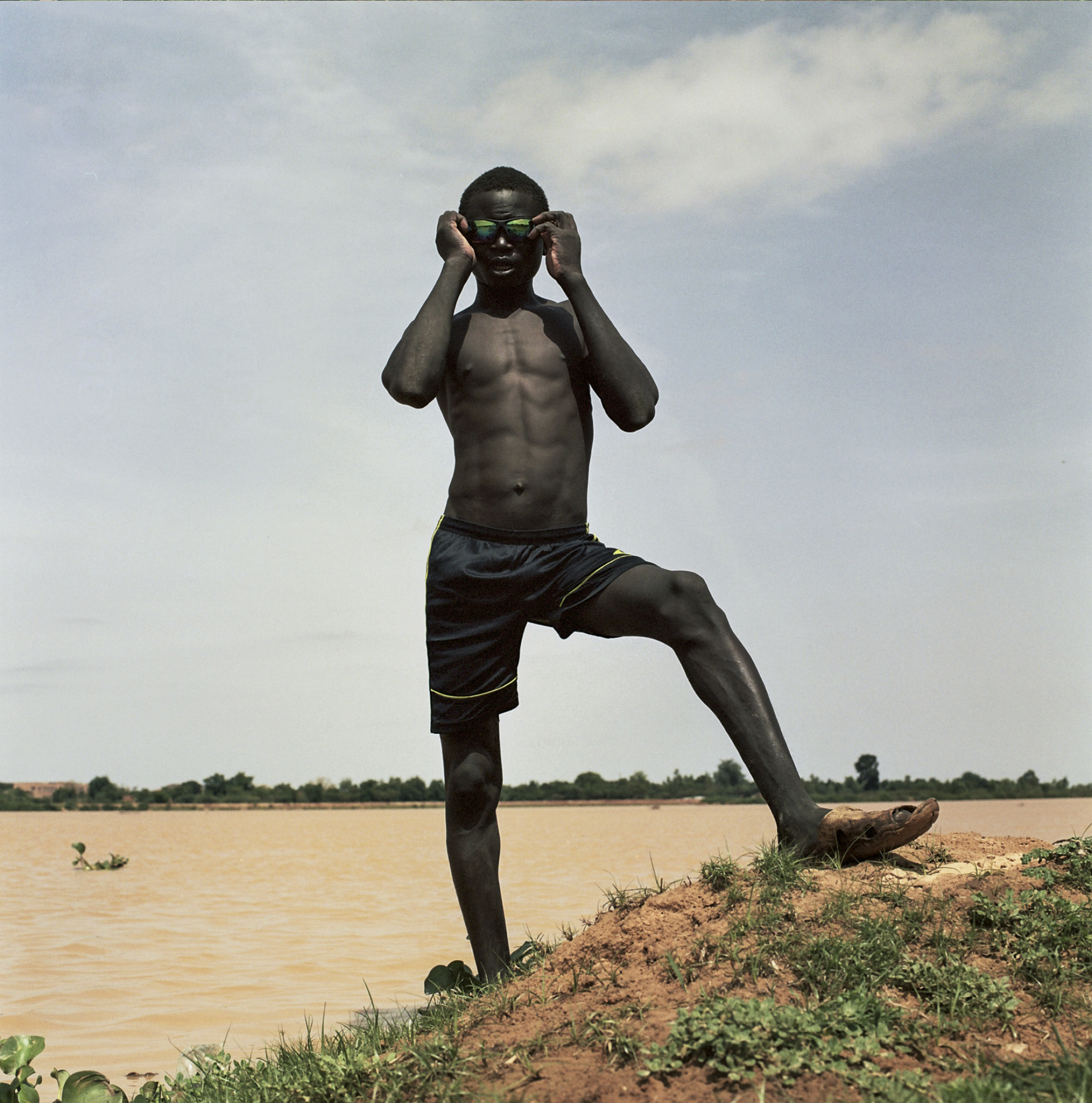 A young boy puts on his sunglasses on the banks of the Niger River.