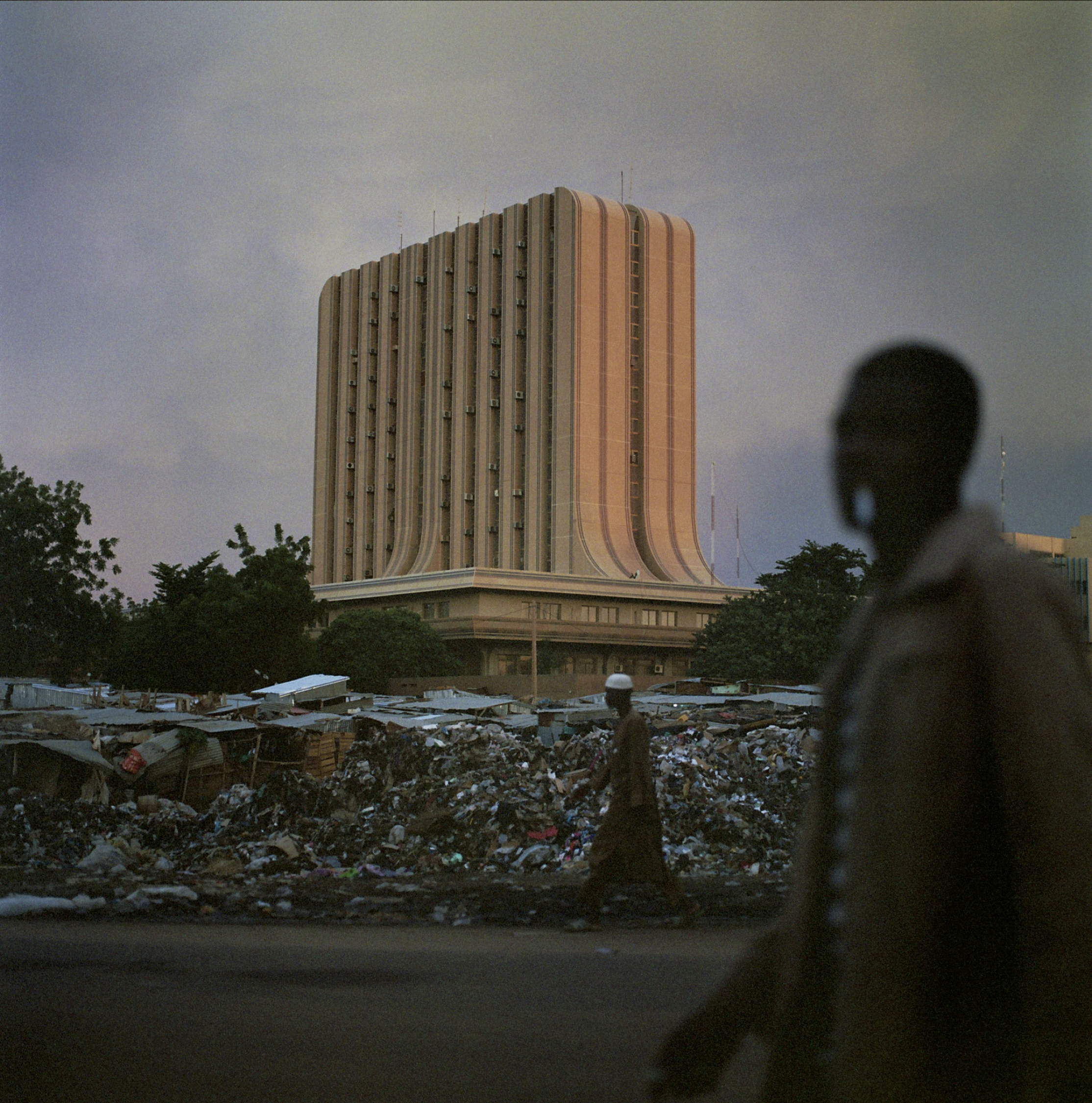 Men walk past trash heaps and tin-roofed huts in downtown Niamey.