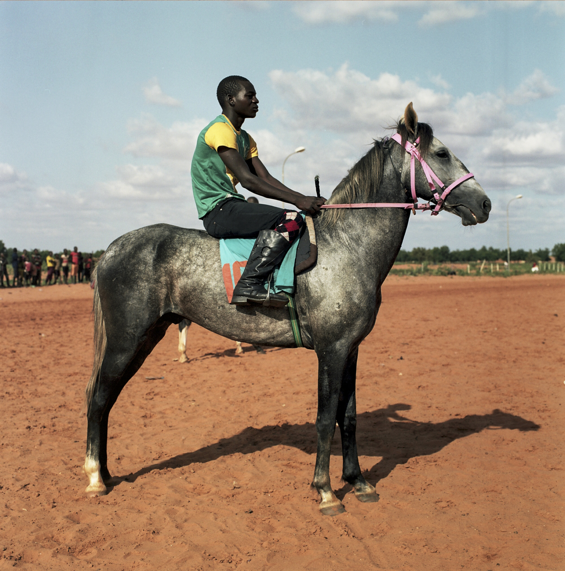 Zacharria rests on his horse, Welcome, before racing in Niamey.