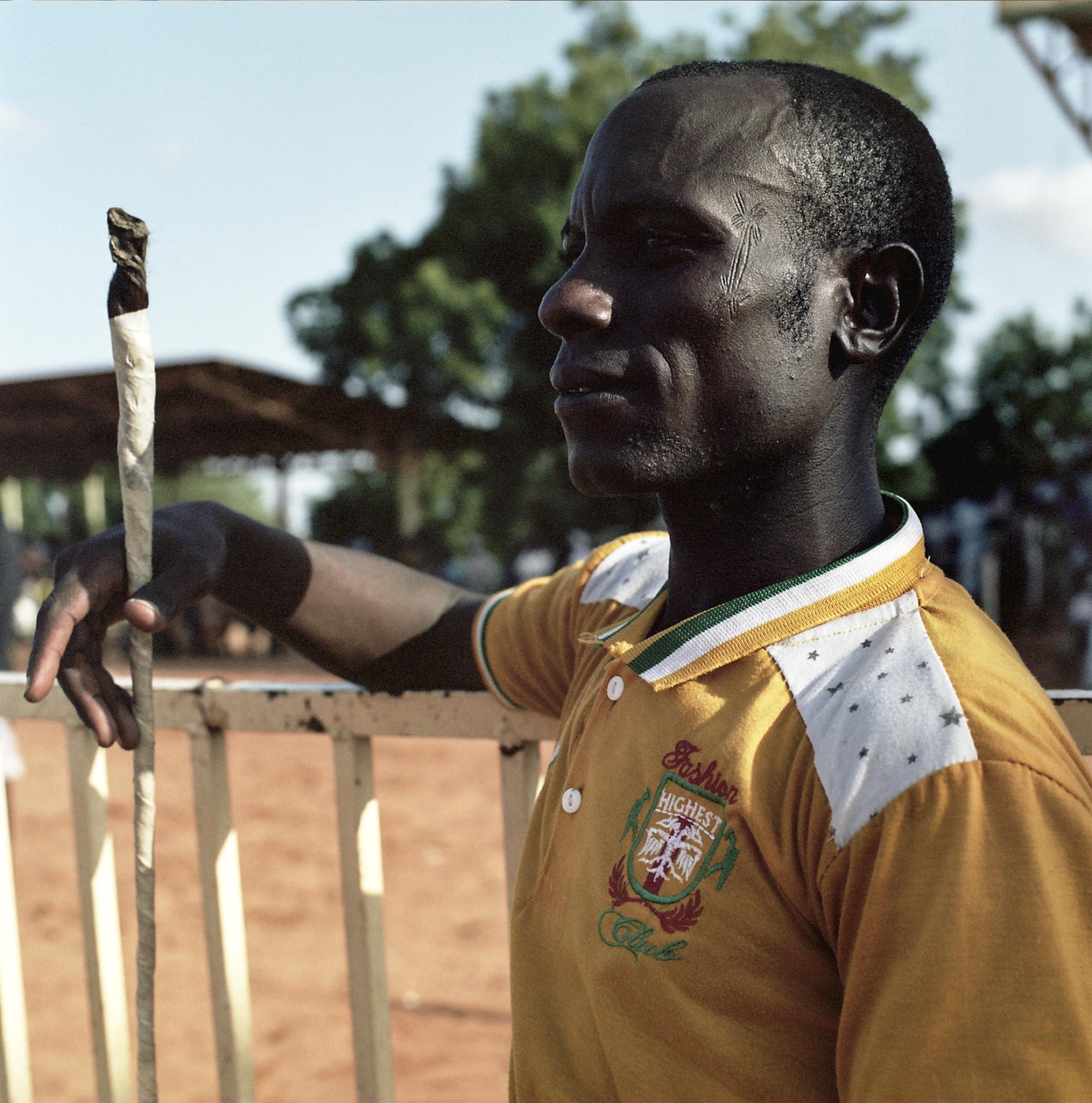 Tribal scars mark the face of a jockey.