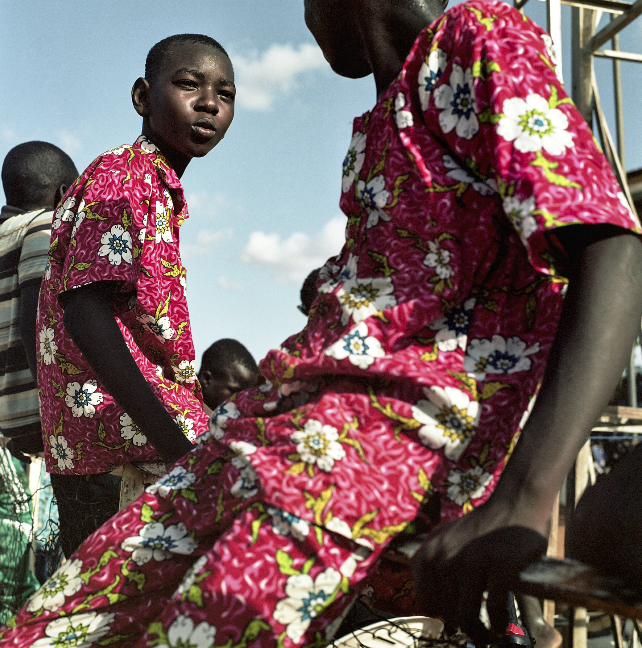 Two brothers sit on a fence and chat between races at a horse track in Niamey.