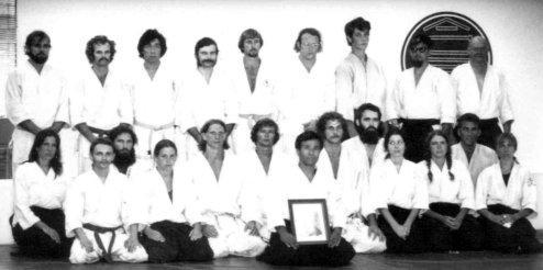 Mc Peck Sensei is shown on the bottom row (second in from the left) and Saotome Shihan is center holding photo a of O'Sensei.