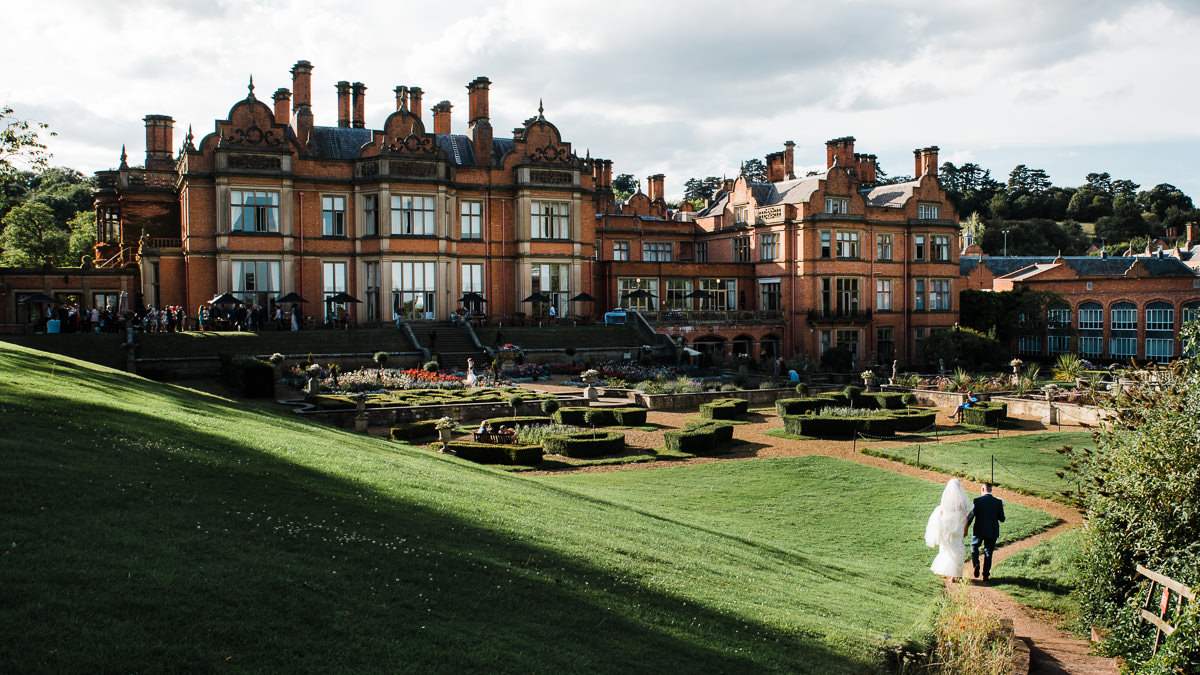 Bride and groom returning to their wedding guests during their summer wedding at The Welcombe Hotel in Stratford-upon-Avon.